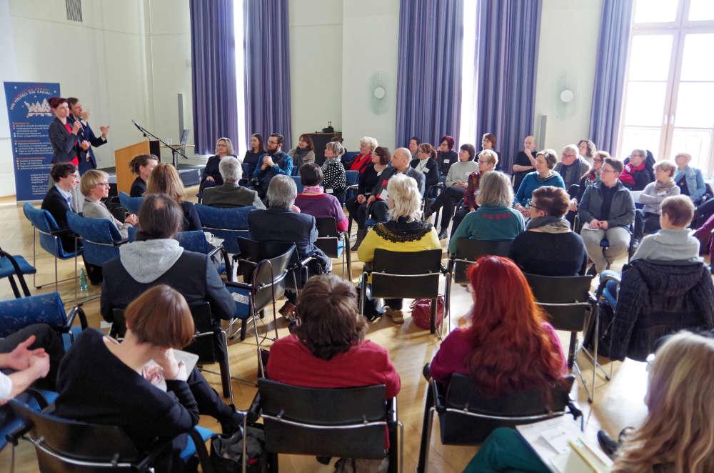 Teilnehmende sitzen im Festsaal des Ministeriums in großer Runde zusammen. Ein Gebärdensprachdolmetscher übersetzt.