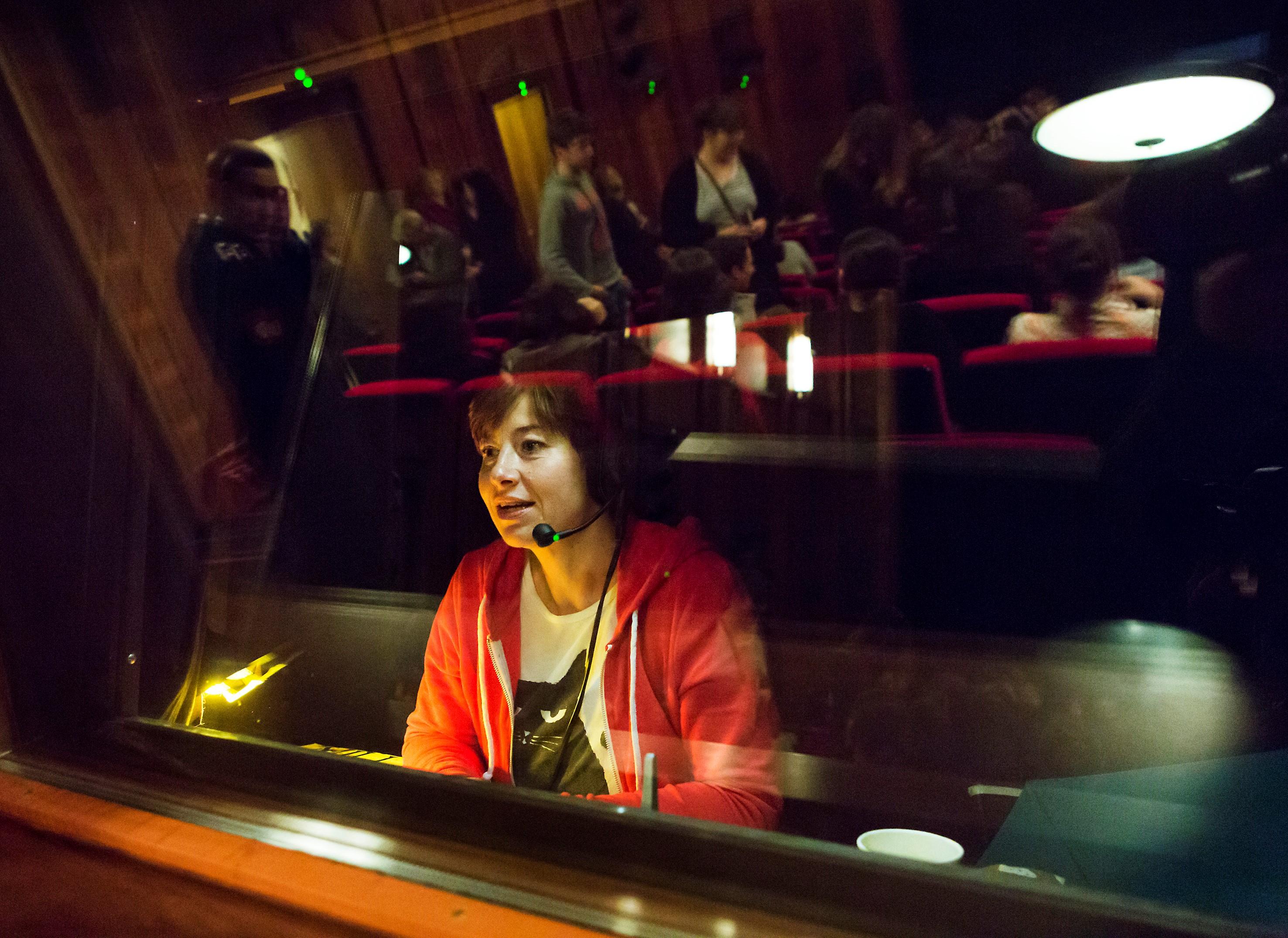 Die Autorin einer live-Audiodeskription in der Sprecherkabine hinter Glas. Sie trägt ein Headset. Links vor ihr ist eine kleine Leselampe. Im Glas der Kabine spiegelt sich das Publikum des Theatersaals.