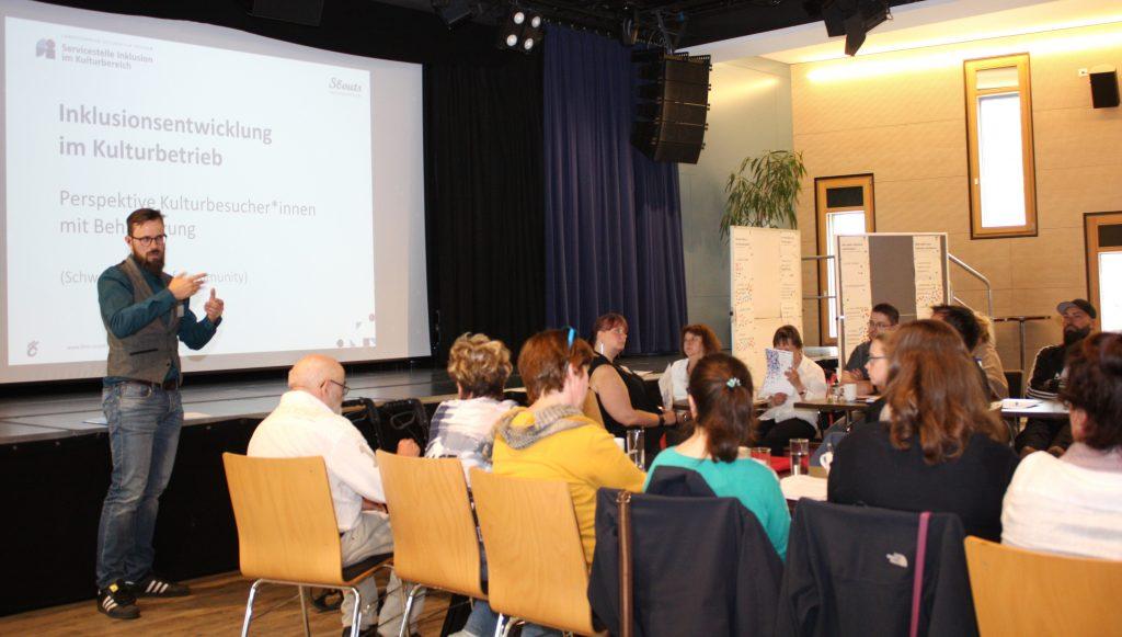 Die Teilnehmenden der Veranstaltung sitzen an einem Tisch. Links zu sehen der Referent Norbert Richter. Im Hintergrund die Powerpoint-Präsentation mit dem Titel Inklusionsentwicklung im Kulturbetrieb aus der Perspektive von KulturbesucherInnen mit Behinderung