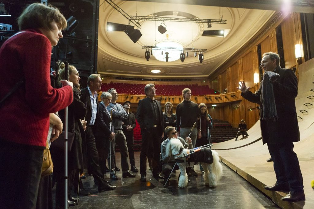 Blinde Thetaerbesucher bekommen eine Bühnenführung. Sie stehen auf der Bühne und hören dem Regisseur zu.