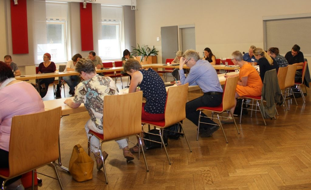 Teilnehmerinnen und Teilnehmer sitzen an einem Tisch und schreiben