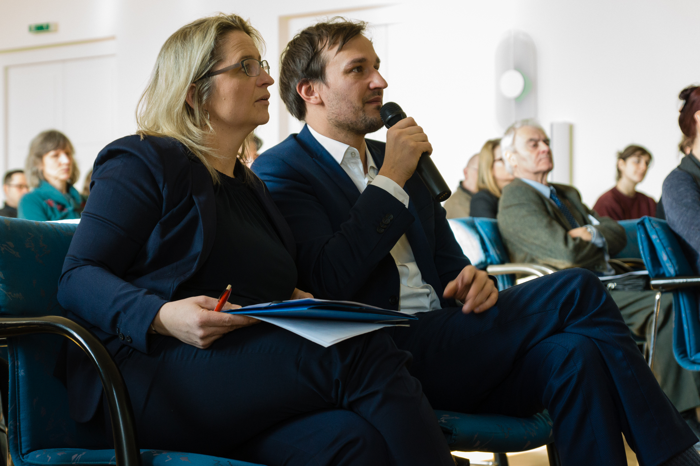 Zwei Dolmetscher sitzen nebeneinander. Einer spricht ins Mikrofon.