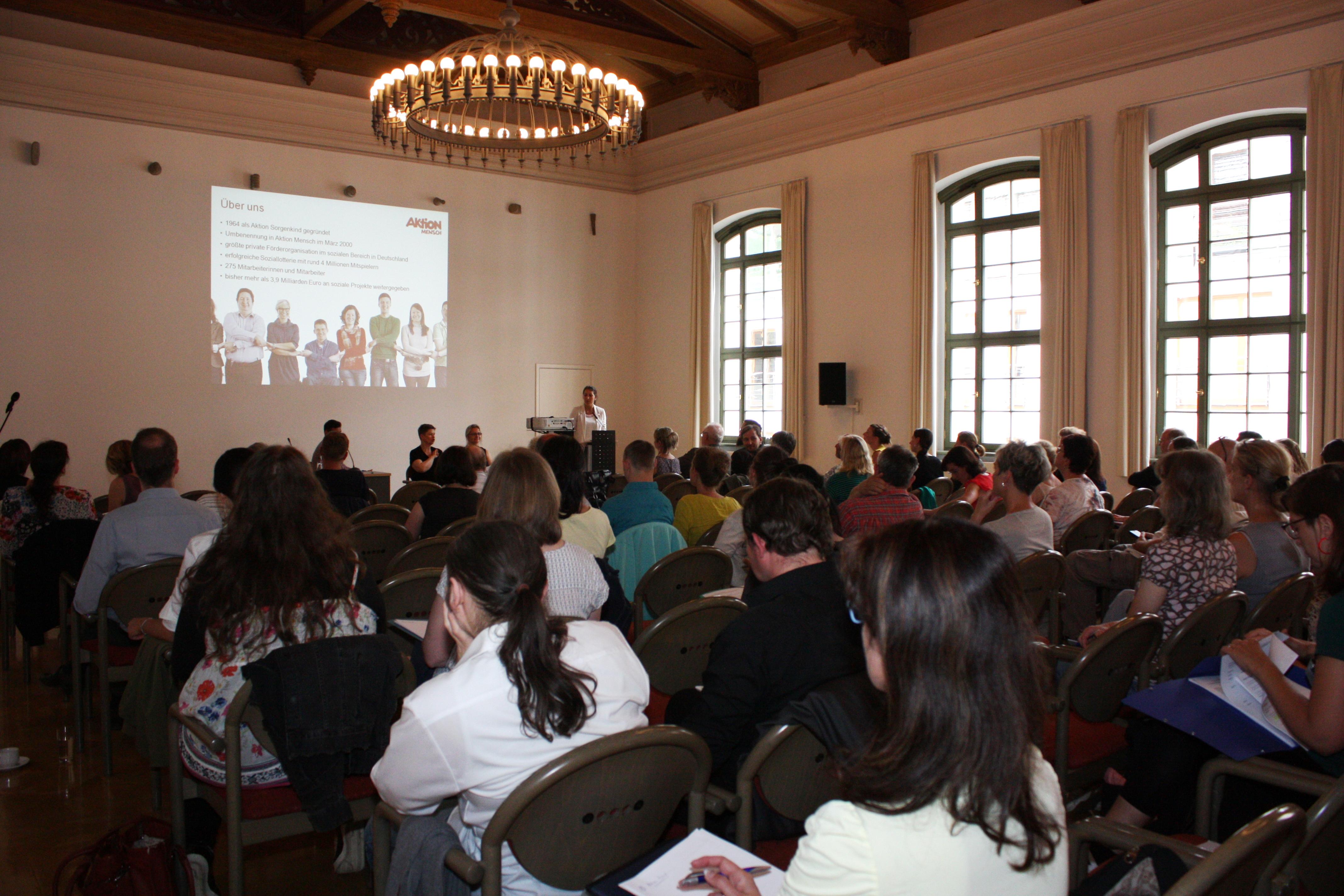 Zu sehen sind die Teilnehmenden von hinten. Vorn steht die Referentin und präsentiert die Programme der Aktion Mensch.