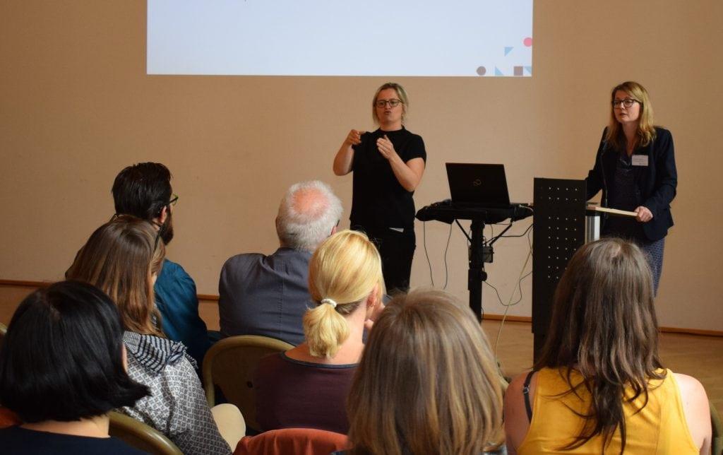 Der Vortrag der Referentin wird von einer Dolmetscherin in Gebärdensprache übersetzt