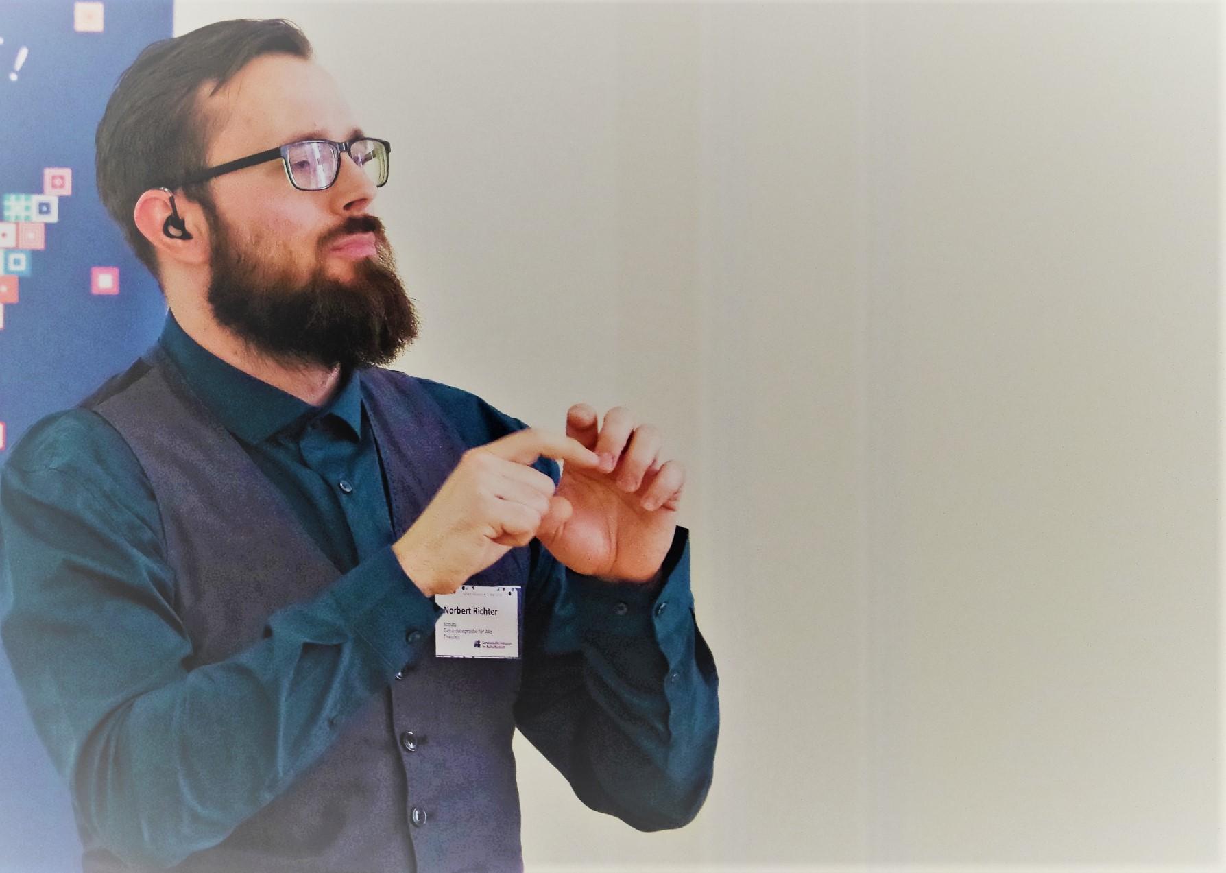 Ein Mann hält einen Vortrag in Gebärdensparche.