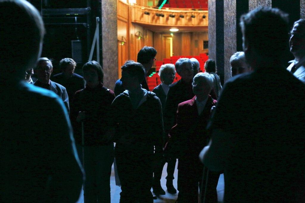 Eine Gruppe blinder und sehbeeinträchtigter Menschen auf der Bühne im Hintergrund der Zuschauerraum.