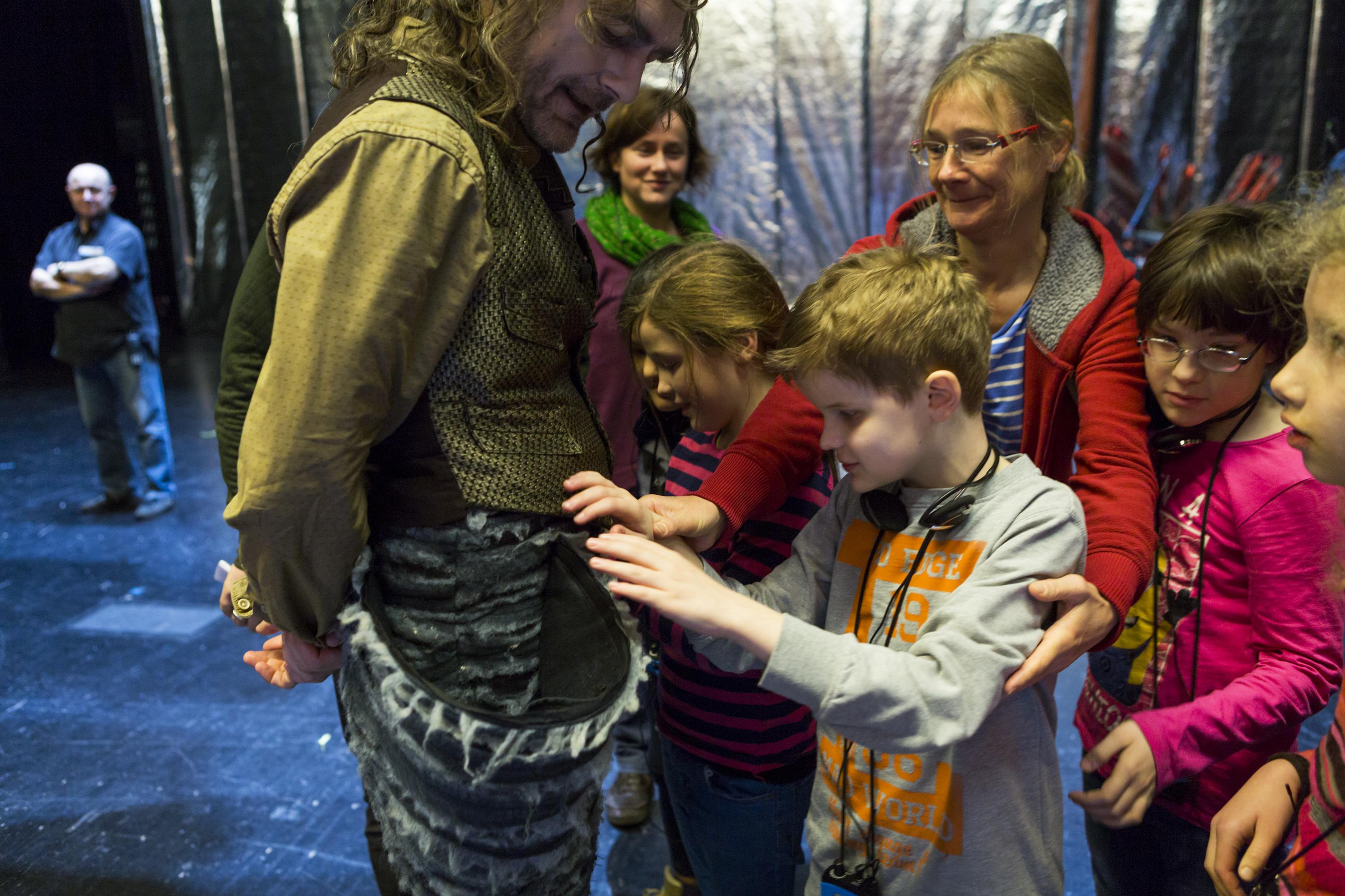 """Kinder ertasten das Kostüm vom Urfin (vor der Vorstellung """"Der schlaue Urfin und seine Holzsoldaten)"""