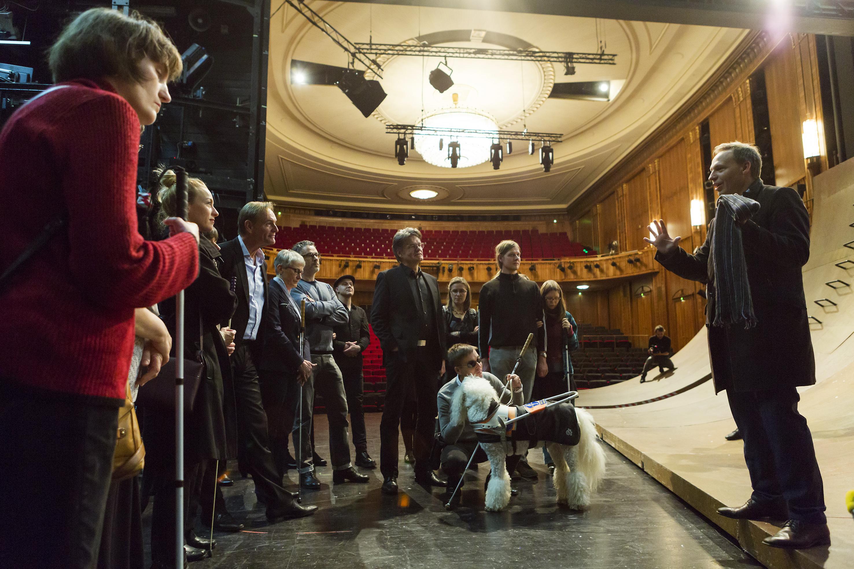 """Blinde Gäste mit ihren Inklusionspaten bei der Bühnenführung und Stückeinführung von Enrico Lübbe, Intendant und Regisseur der Inszenierung """"Die Schutzflehenden /Die Schutzbefohlenen"""""""