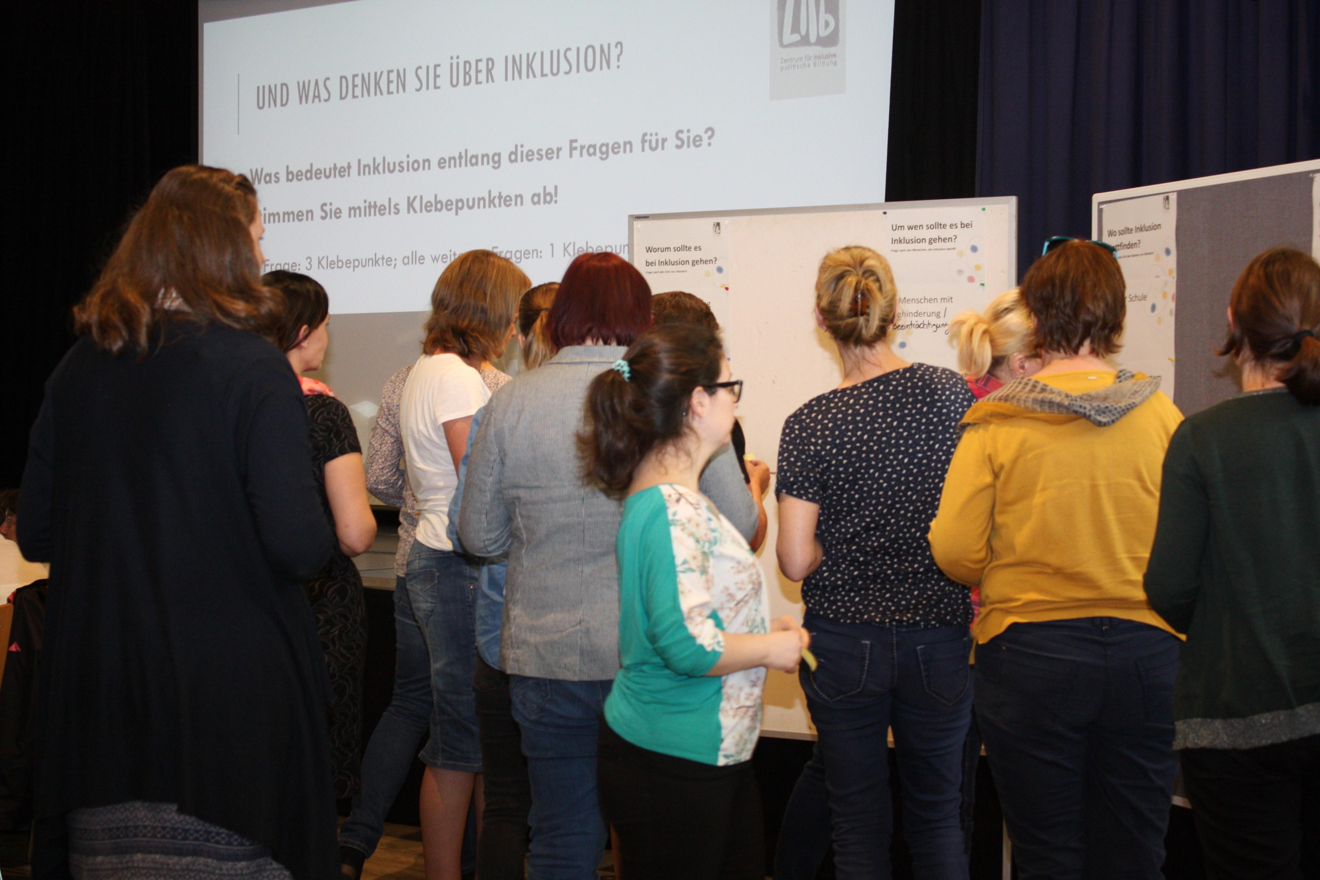Die Teilnehmenden stehen an Stellwänden und stimmen ab, was Inklusion für sie bedeutet