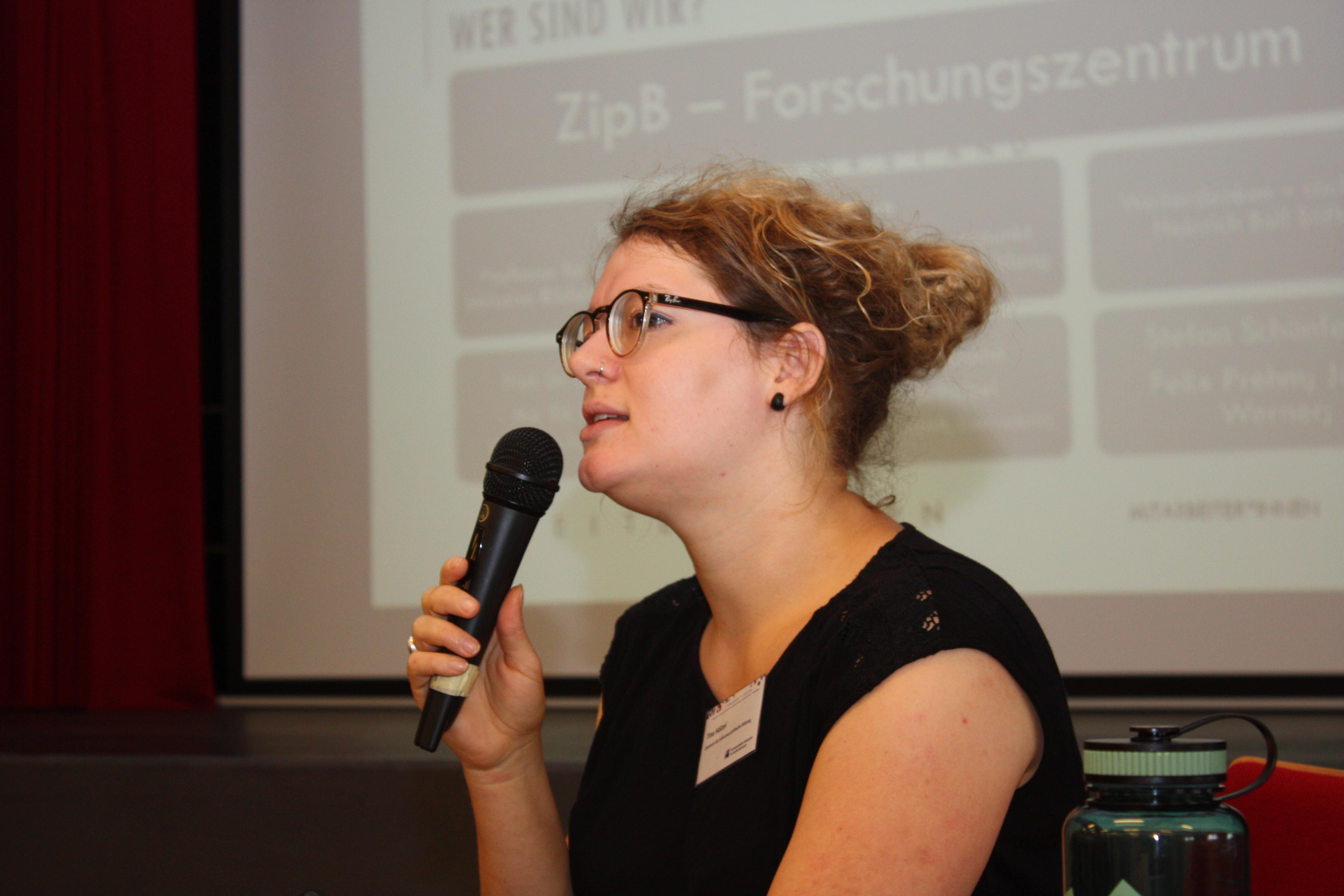 Referentin spricht ins Mikrofon