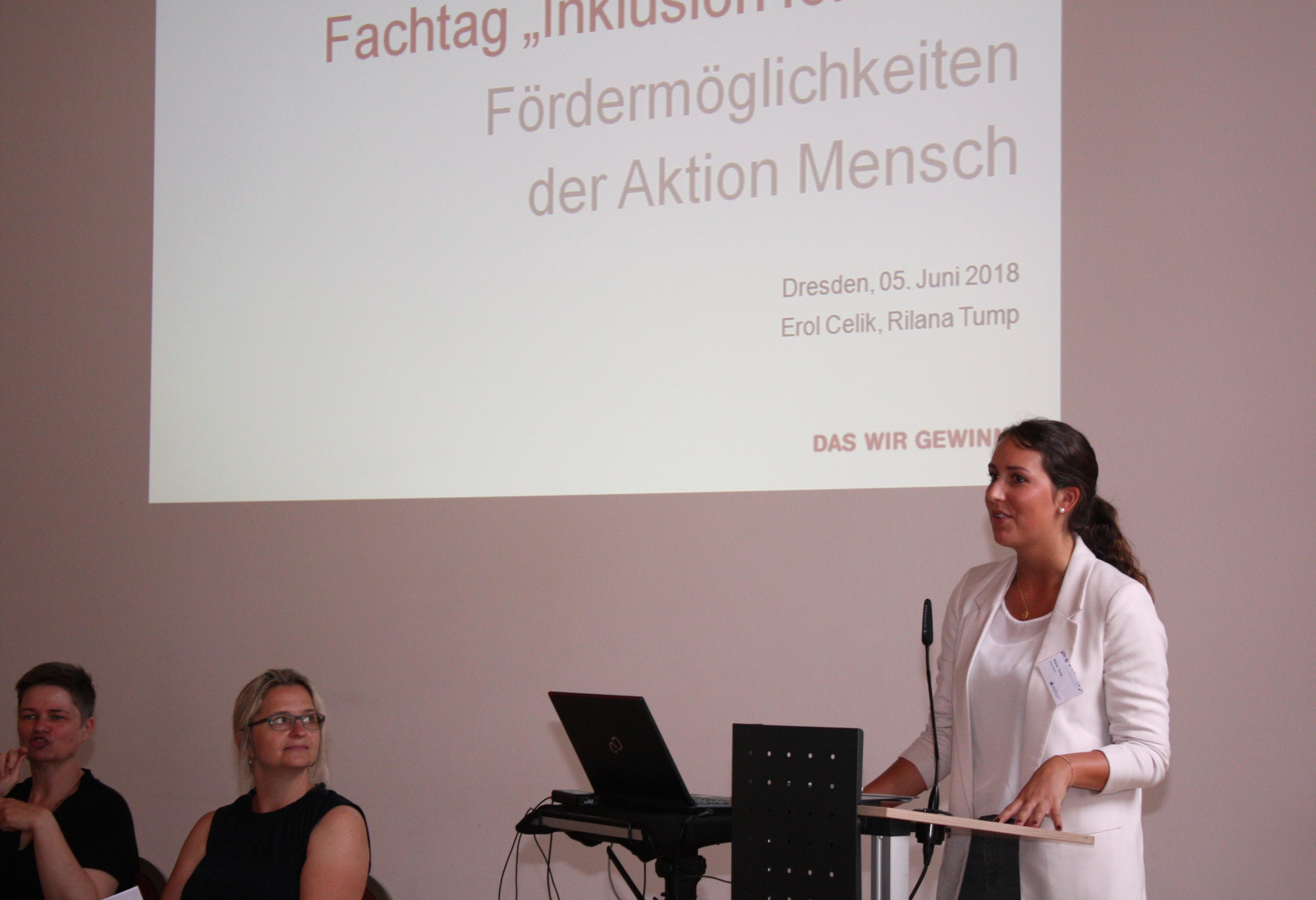 Referentin am Pult stehend, im Hintergrund Präsentation, links zwei Gebärdensprachdolmetscherinnen