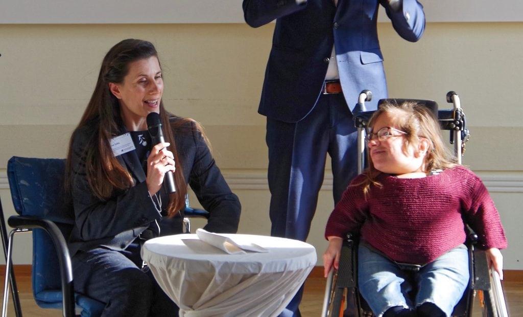 Zwei Frauen in einer Podiumsdiskussion. Die Moderatorin (sitzend) interviewt eine Frau im Rollstuhl.
