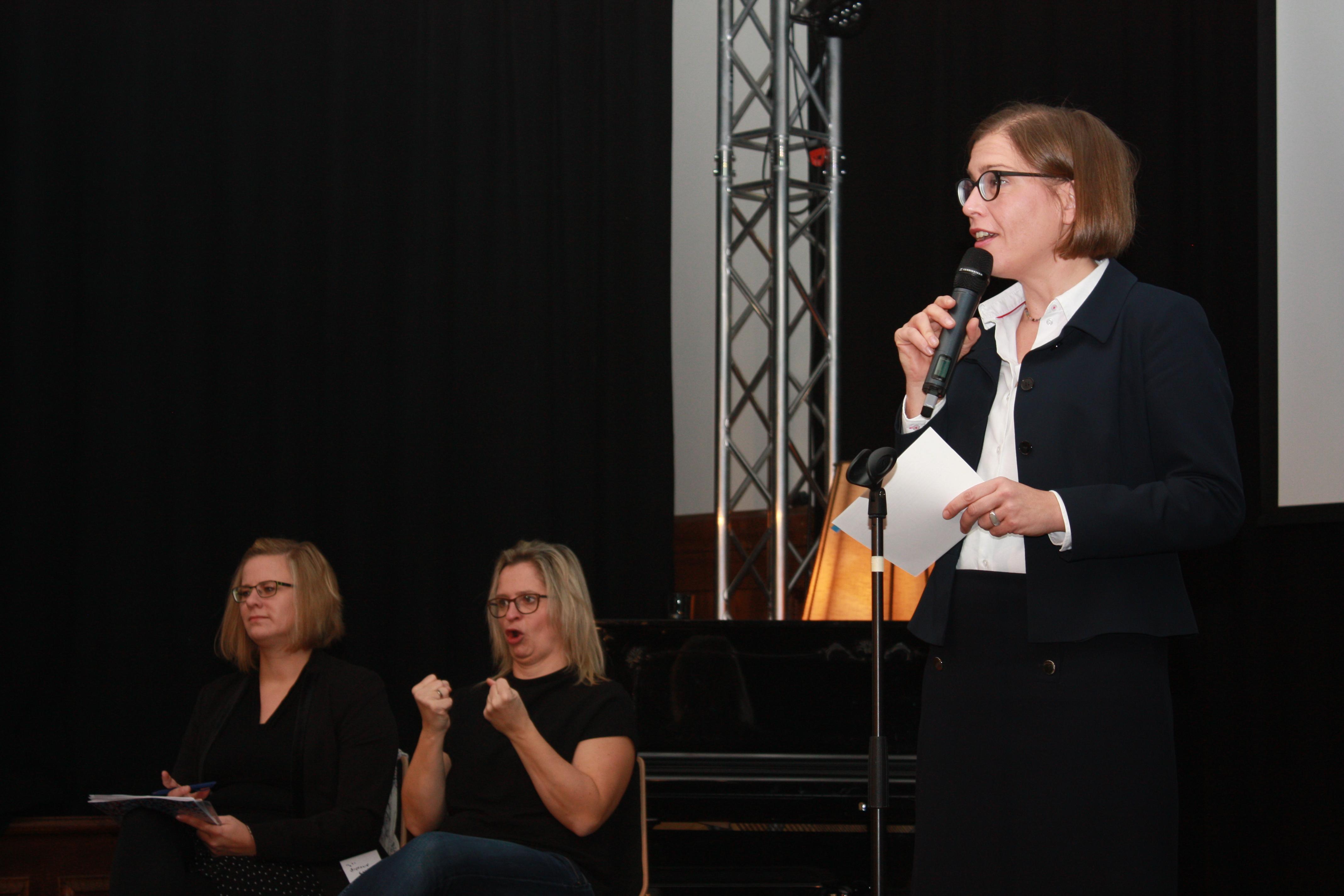 Dr. Skadi Jennicke hält das Grußwort. Im Hintergrund zwei gebärdensprachdolmetscherinnen.