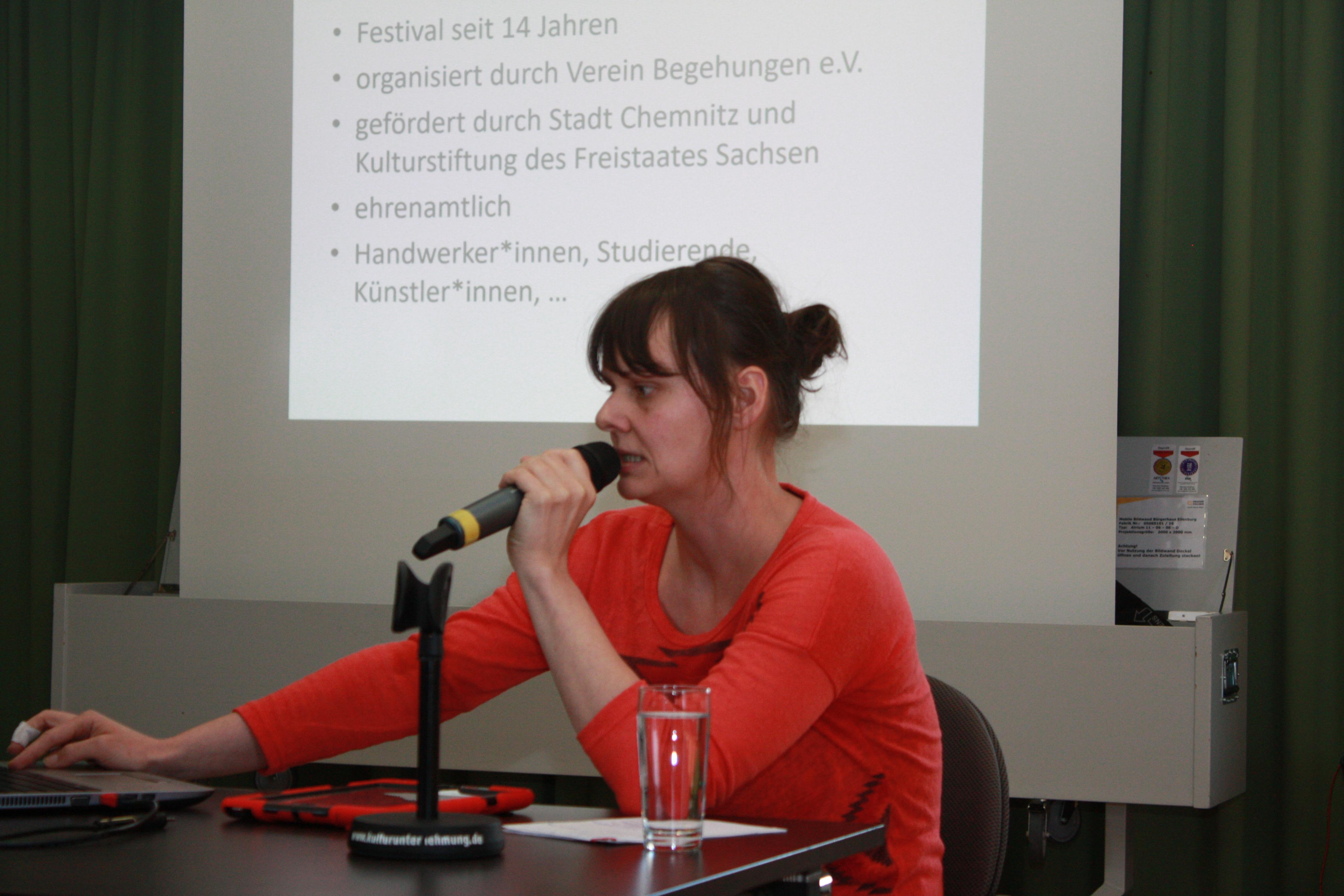Eine Referentin sitzend vor Präsentation. Spricht ins Mikrofon.