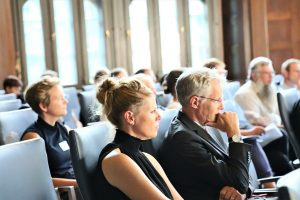 Blick ins Publikum. Im Vordergrund ist das Publikum, von der Seite aufgenommen; zu sehen.