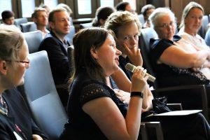Blick ins Publikum. Eine Teilnehmerin hält eine Mikrophon in der Hand