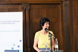 Staatsministererin Dr. Eva-Maria Stange steht am Rednerpult und schaut lächelnd nach rechts.