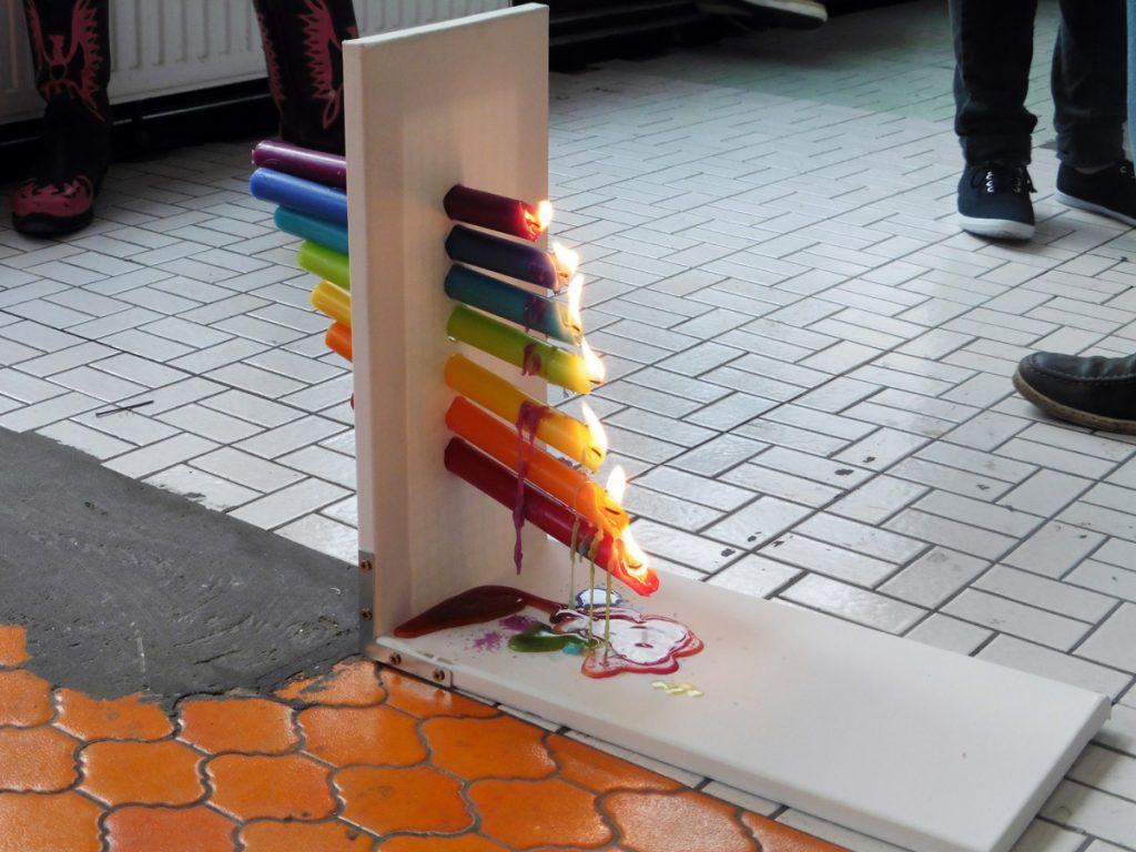 """Installation """"PRISMA"""": Sieben farbige Kerzen stecken waagerecht in einer Leinwand, die auf dem Boden steht. Die Kerzen haben die Farben des Regenbogens, sind treppenförmig angeordnet und brennen. Der geschmolzene Wachs tropft von oben nach unten und vermischt sich dabei."""