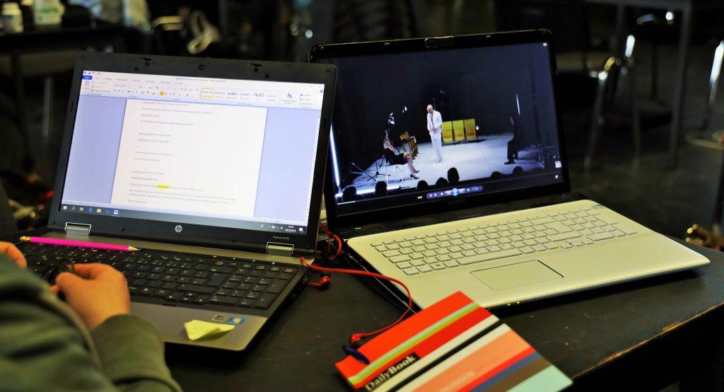 Auf einen Tisch stehen zwei Laptops nebeneinander. Sie sind aufgeklappt. der rechte Laptop zeigt ein Video, der linke einen Text. Zwischen den Laptops liegt ein Notizbuch.