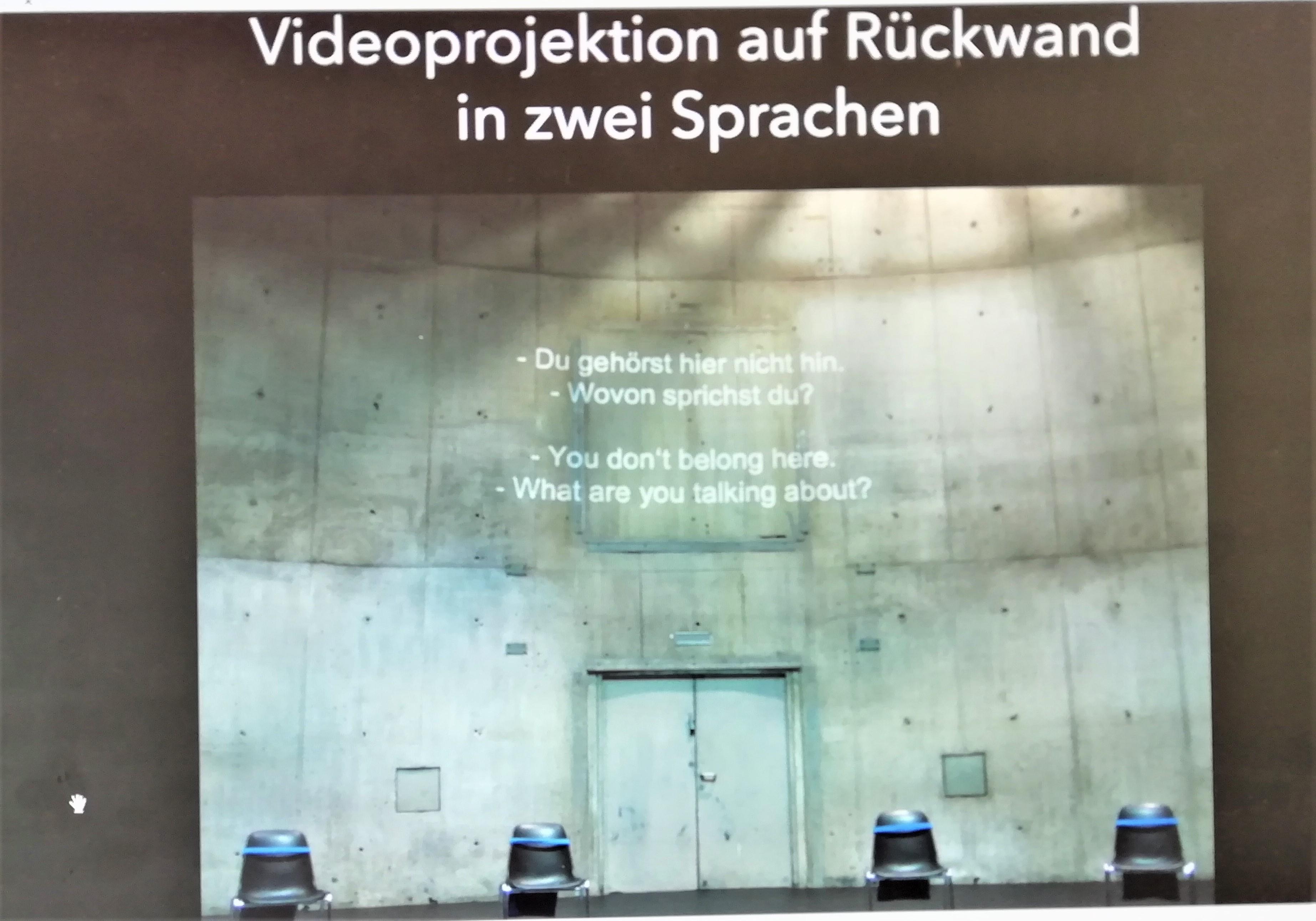 Auf einer Bühne stehen vier dunkle Stühle. Der Bühnenhintergrund ist eine hohe graue Sichtbetonwand. Auf die Wand sind weiße Übertitel projiziert.