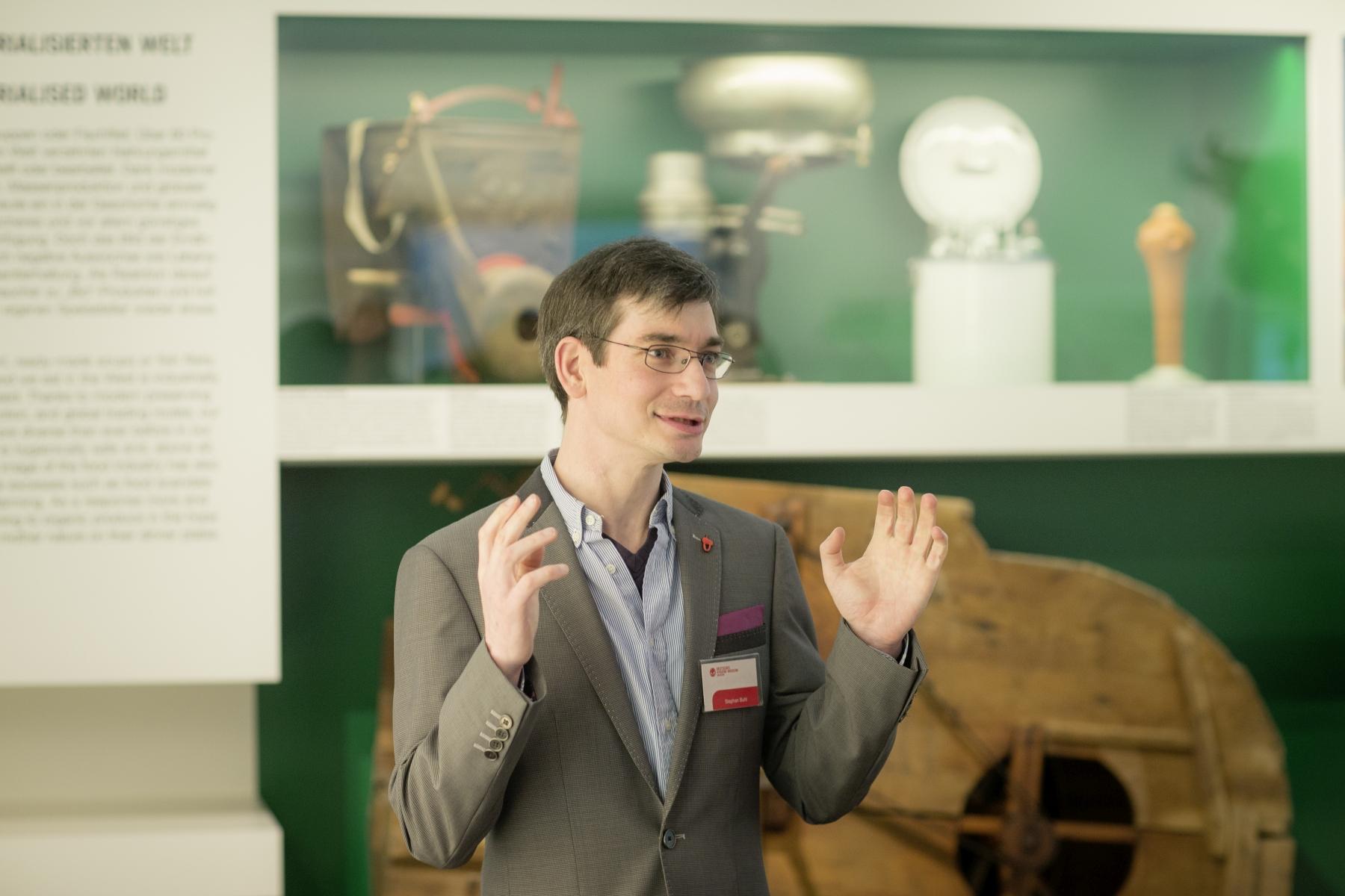 Ein Kulturvernittler steht vor einer Austellungsvitrine. Er spricht mit erhobenen Händen, die offensichtlich das, was er sagt, unterstreichen sollen.