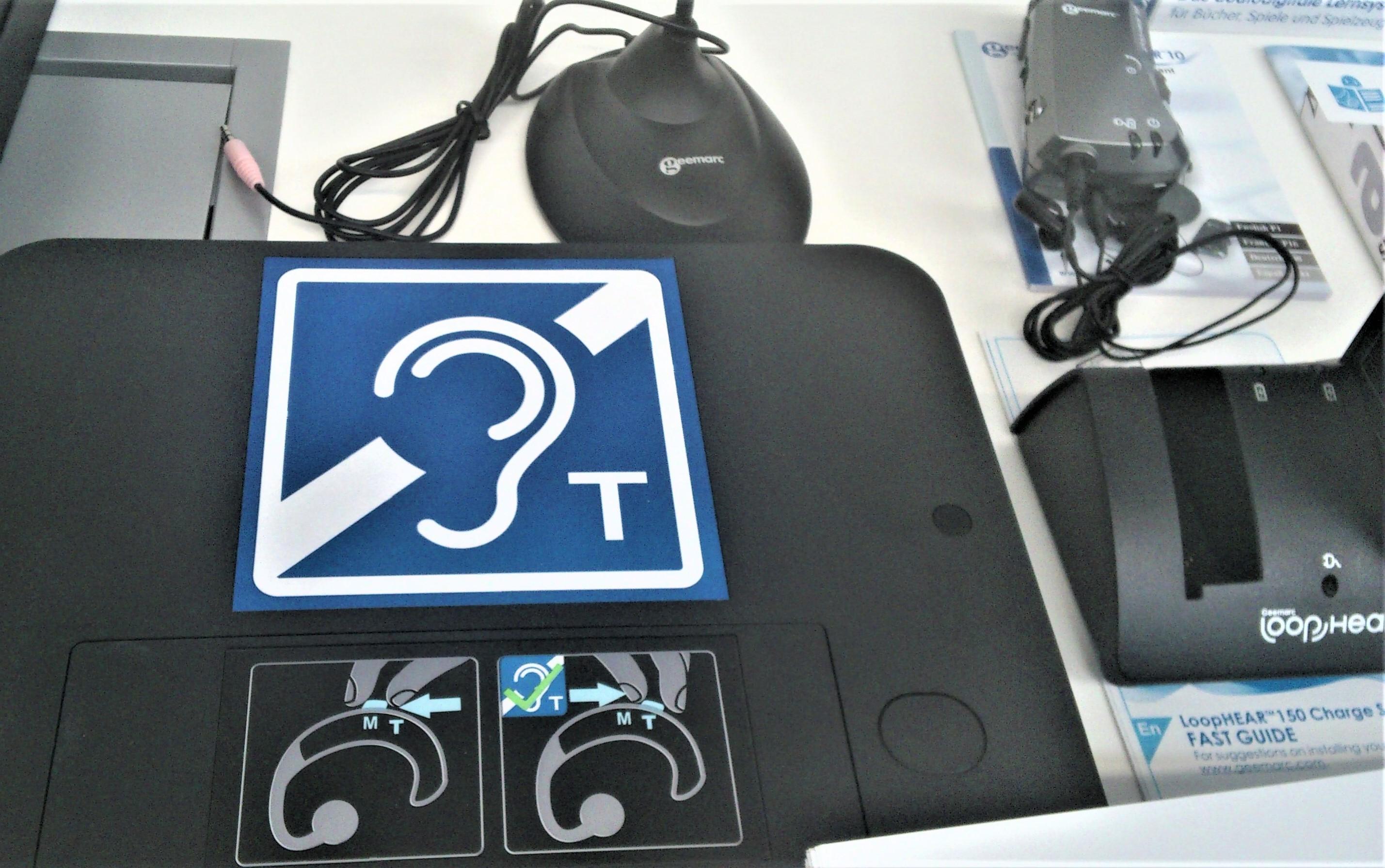 Im Vordergrund das Piktogramm für Induktive Hörschleife. Dahinter die mobile Höranlage.