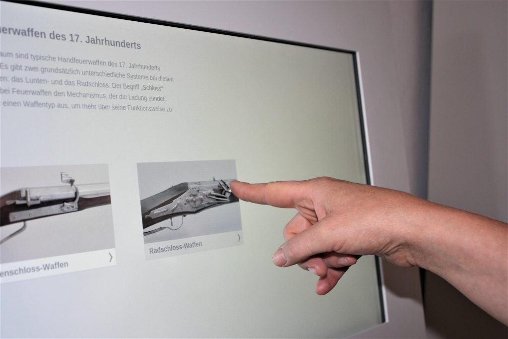 Zu sehen ist ein Touch Screen. Es werden Informationen und Bilder angezeigt. Ein Finger tippt auf das Bild.