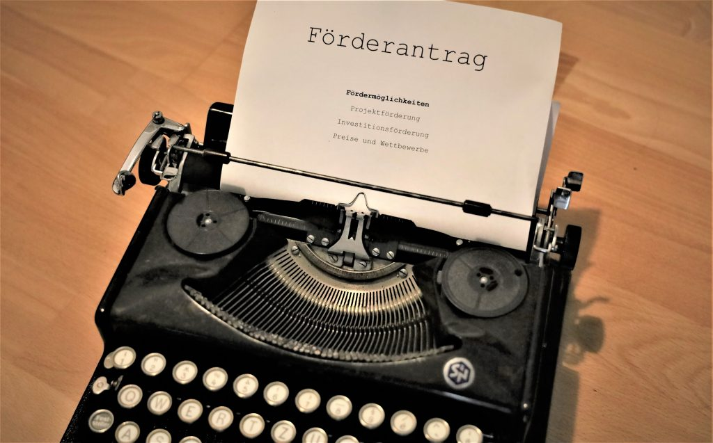 Eine Schreibmaschine mit eingespanntem Blatt. Darauf ist zu lesen: Förderantrag. Fördermöglichkeiten: Projektförderung, Investitionsförderung, Wettbewerbe und Preise.