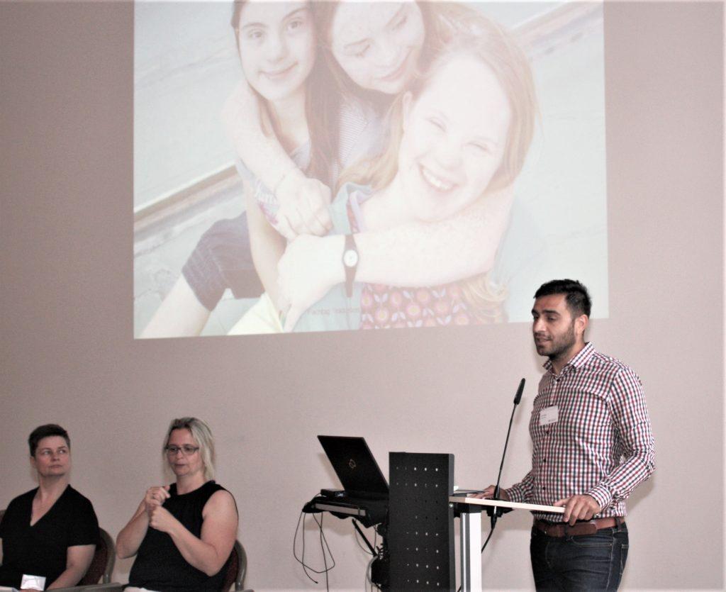 Der Referent steht am Pult. Links neben ihm sitzen zwei Gebärdensprachdolmetscherinnen und dolmetschen. Im Hintergrund ist die PowerPointPräsentation zu sehen. Sarauf drei Mädchen, die sich umarmen.
