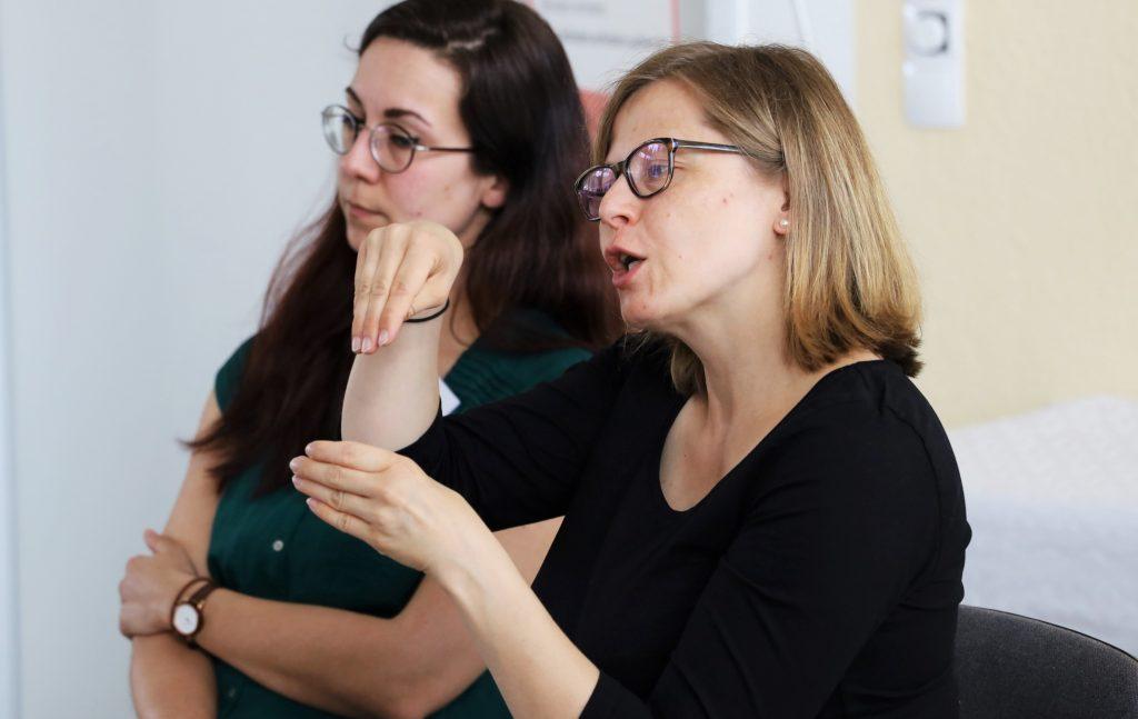Zwei Gebärdensparchdolmetscherinnen sitzend. Eine der beiden übersetzt in Gebärdensprache.