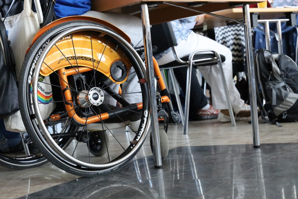 Verschiedene Personen sitzen an Tischen. Zu sehen sind jedoch nur die Tischbeine und Beine der Personen bzw. Räder eines Rollstuhls.