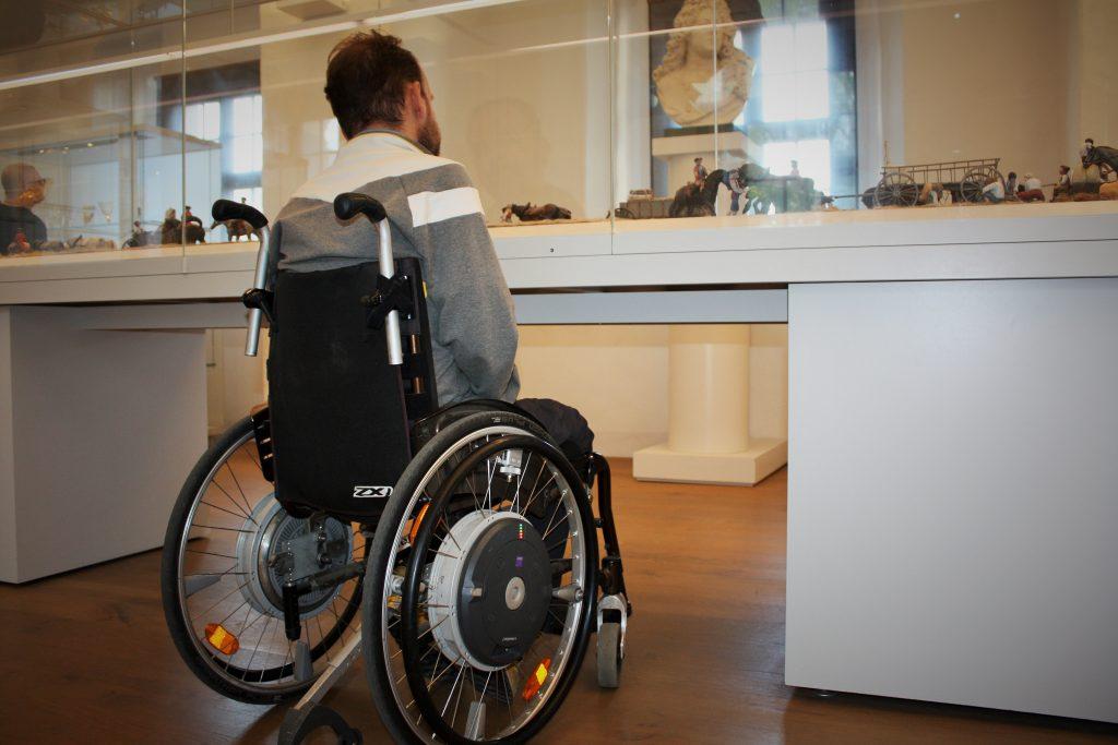 Ein Rollstuhlfahrer steht vor einer unterfahrbaren Ausstellungsvitrine. Er ist von hinten fotografiert.