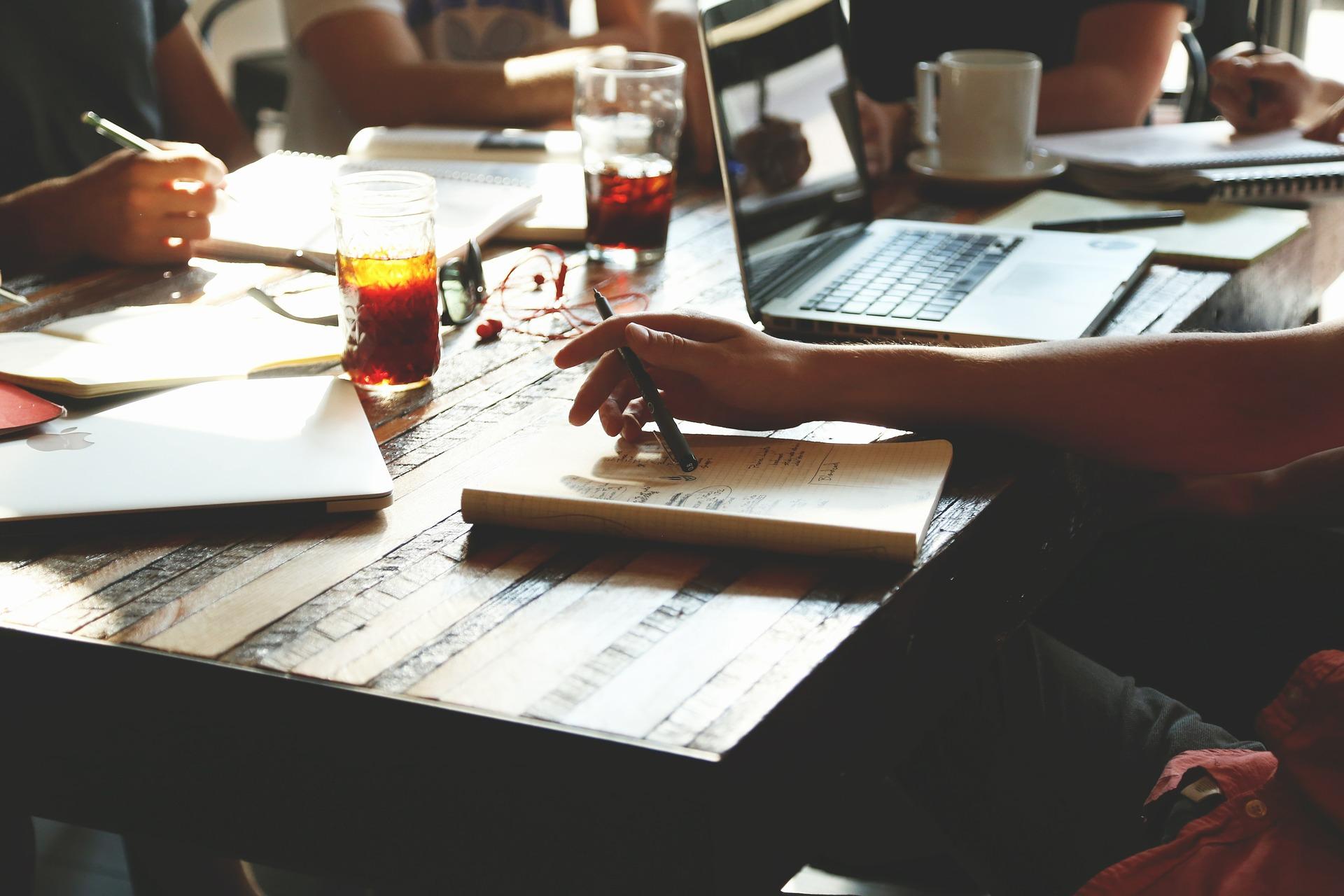 An einem Tisch sitzen sich vier Personen gegenüber. Von den Personen, die am Tisch sitzen, sind nur die Arme zu sehen. Die Personen halten einen Stift in der Hand. Auf dem Tisch liegen Notizblätter, ein Laptop, Kaffeetasse und zwei Gläser mit brauner Flüssigkeit.