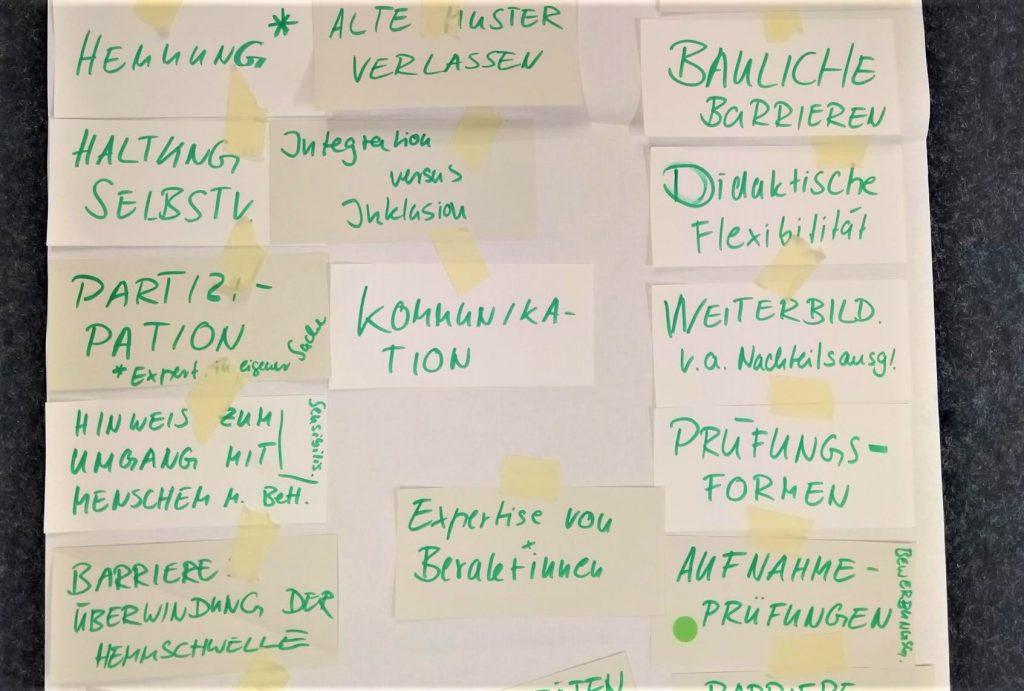 Flipchart mit aufgeklebten Notizzetteln, die mit grünem Stift beschrieben sind.