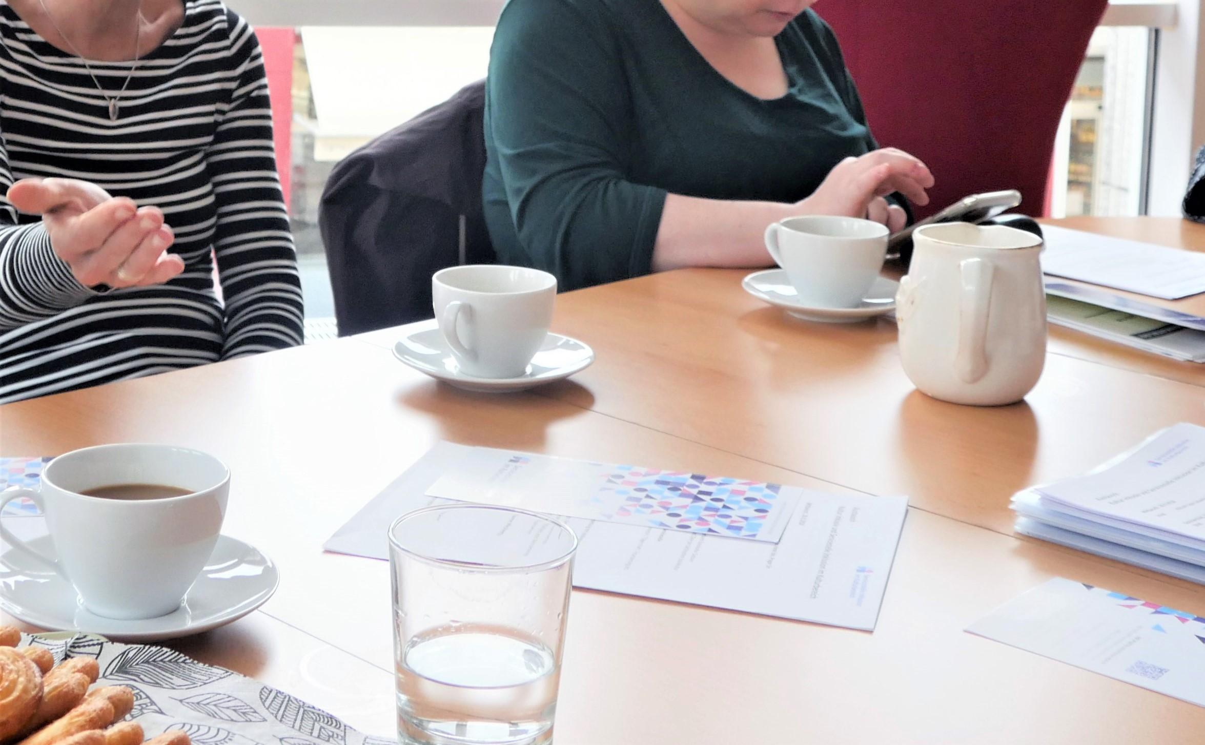 Ein Tisch. darauf einige Kaffeetassen und Schreibzeug. Um den Tisch herum sitzen zwei Personen. Es sind nur ihre Arme und Hände zu sehen.