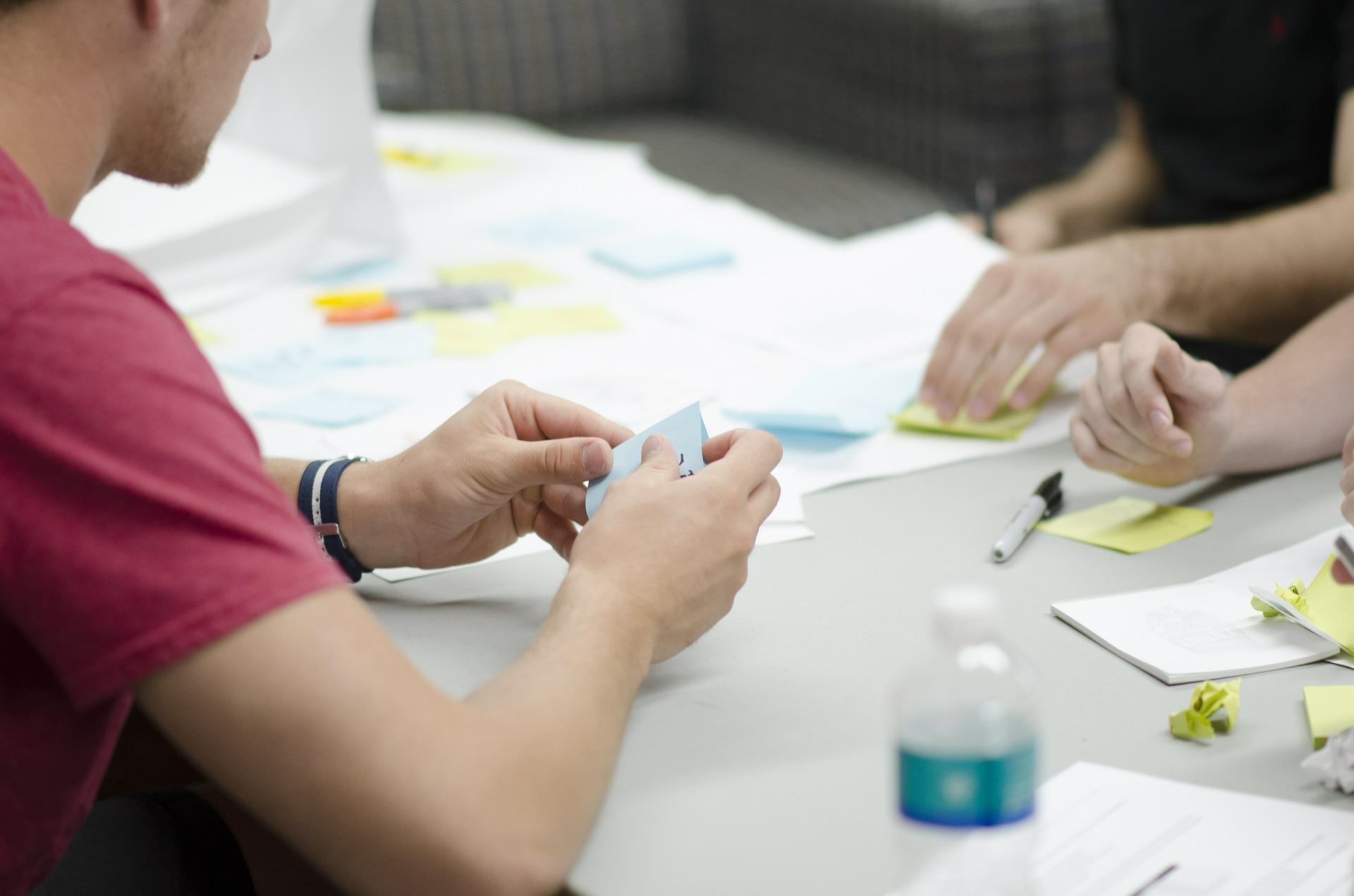 Das Foto zeigt einen Tisch. darauf liegen diverse Schreibmaterialien wie Klebezettel und Papier. Man sieht zwei Händepaare, die Klebezettel aufkleben.