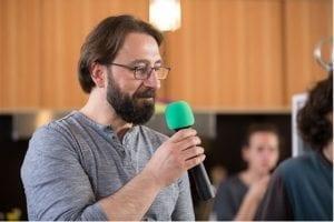 Auf dem Foto ist Düzgün Polat leicht von der Seite als Brustbild zu sehen. Er hält ein Mikro und spricht. Im Hintergrund befindet sich ein Saal und sitzende Zuhörer.