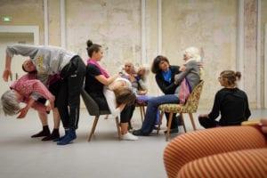 Foto, beim Fachtag Divers! am 18.12.2019 aufgenommen. Eine Gruppe führt den Tagungsteilnehmern ein Theaterstück vor. Es sind 9 Frauen, zum Teil Seniorinnen. Drei sitzen auf Sesseln. drei weitere umarmen jeweils eine sitzende Frau, beziehungsweise ien liegt auf dem Schoss einer sitzenden. Links stehen zwei gebeugte, ineinander verhakte Frauen.