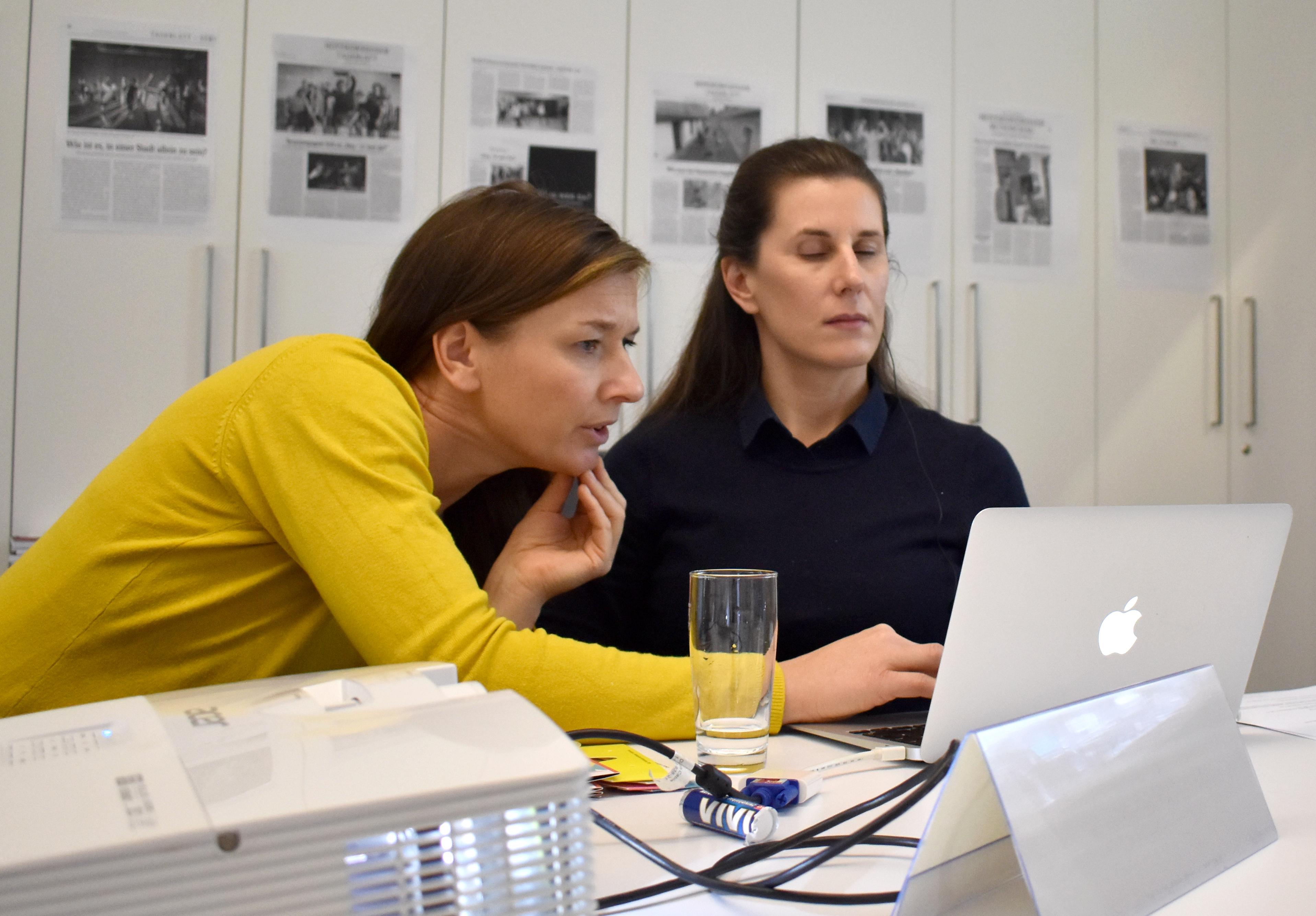 Das Foto zeigt zwei nebeneinandersitzende Personen vor einem Laptop. Workshops. Im Vordergrund steht ein Beamer.