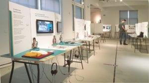 """Zu sehen ist ein ausschnitt der Ausstellung """"Geschichten, die fehlen"""" im stadtmuseum Halle am 20. August 2020. Die Objekte sind auf Tischen angeordnet. Im Hintergrund rechts betrachtet Dirk Sorge einen Tisch."""