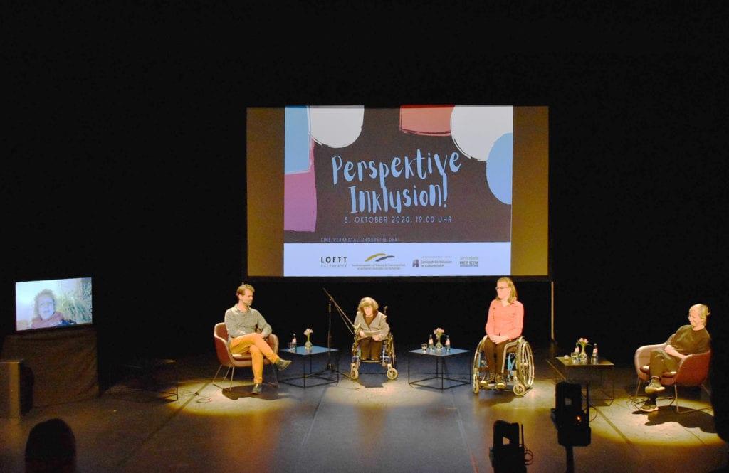 Zu sehen ist die Bühne im LOFFT-DAS THEATER. Der Raum ist dunkel, nur die Personen sind beleuchtet. Im Hintergrund befindet sich eine Leinwand auf die der Titel der Veranstaltung Perspektive Inklusion und die Kooperationspartner projeziert sind. Davor sitzen die Podiumsteilnehmer. In der Mitte die Moderatorin Eva Jünger im Rollstuhl, zu ihrer rechten Gustavo Fijalkow und zu ihrer linken Lisa Zocher (im Rollstuhl). Ganz außen links neben Gustavo Fijalkow steht auf einem Tisch ein großer Bildschirm, in dem Gerda König zu sehen ist. Ganz außen rechts neben Lisa Zocher sitzt Katharina Christl. Zwischen den Podiumsgästen steht jeweils ein kleiner Tisch mit Blume und Getränken.