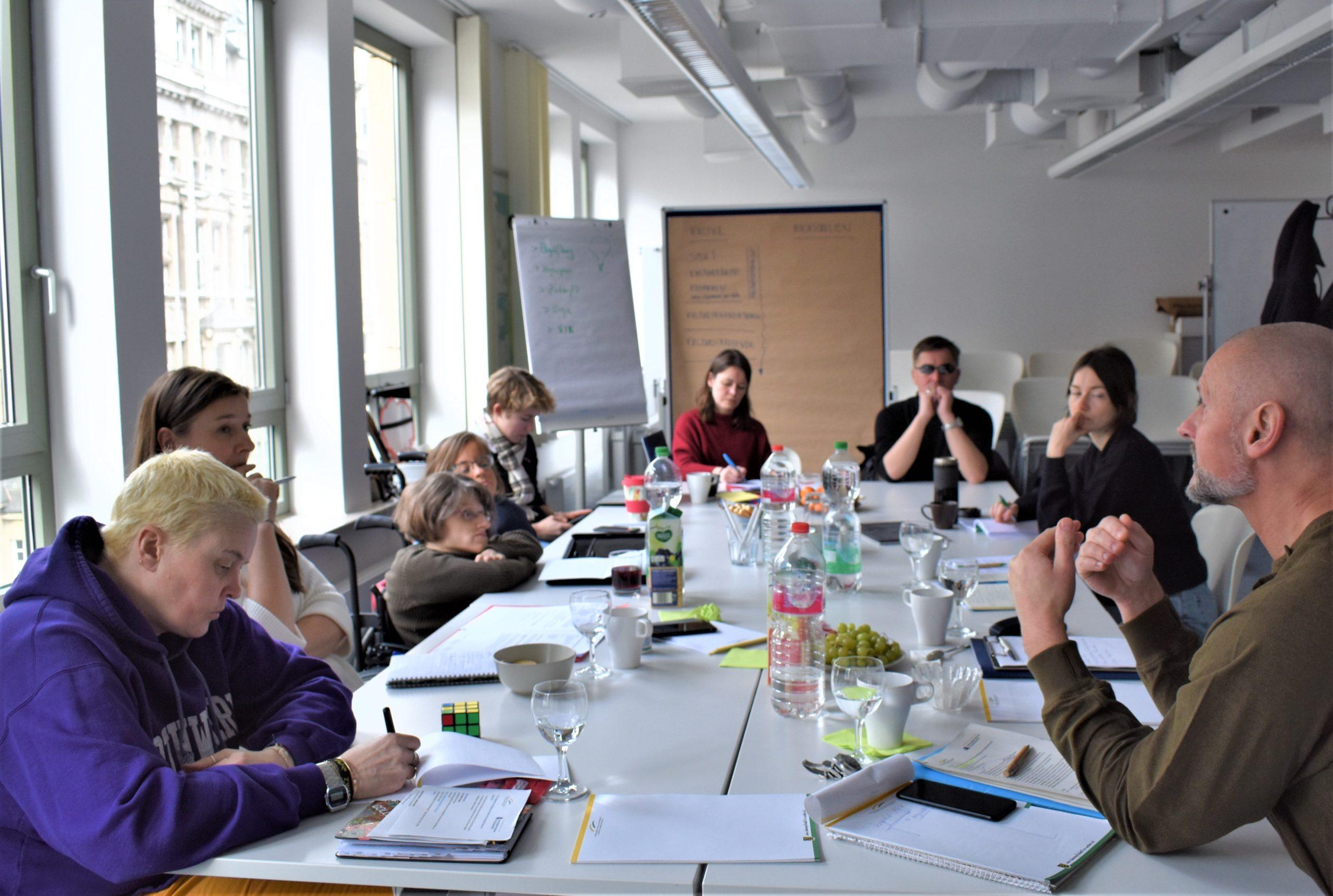 Das Foto zeigt einen langen Tisch. Um den Tisch herum sitzen in U-Form die Mitglieder des Runden Tisches