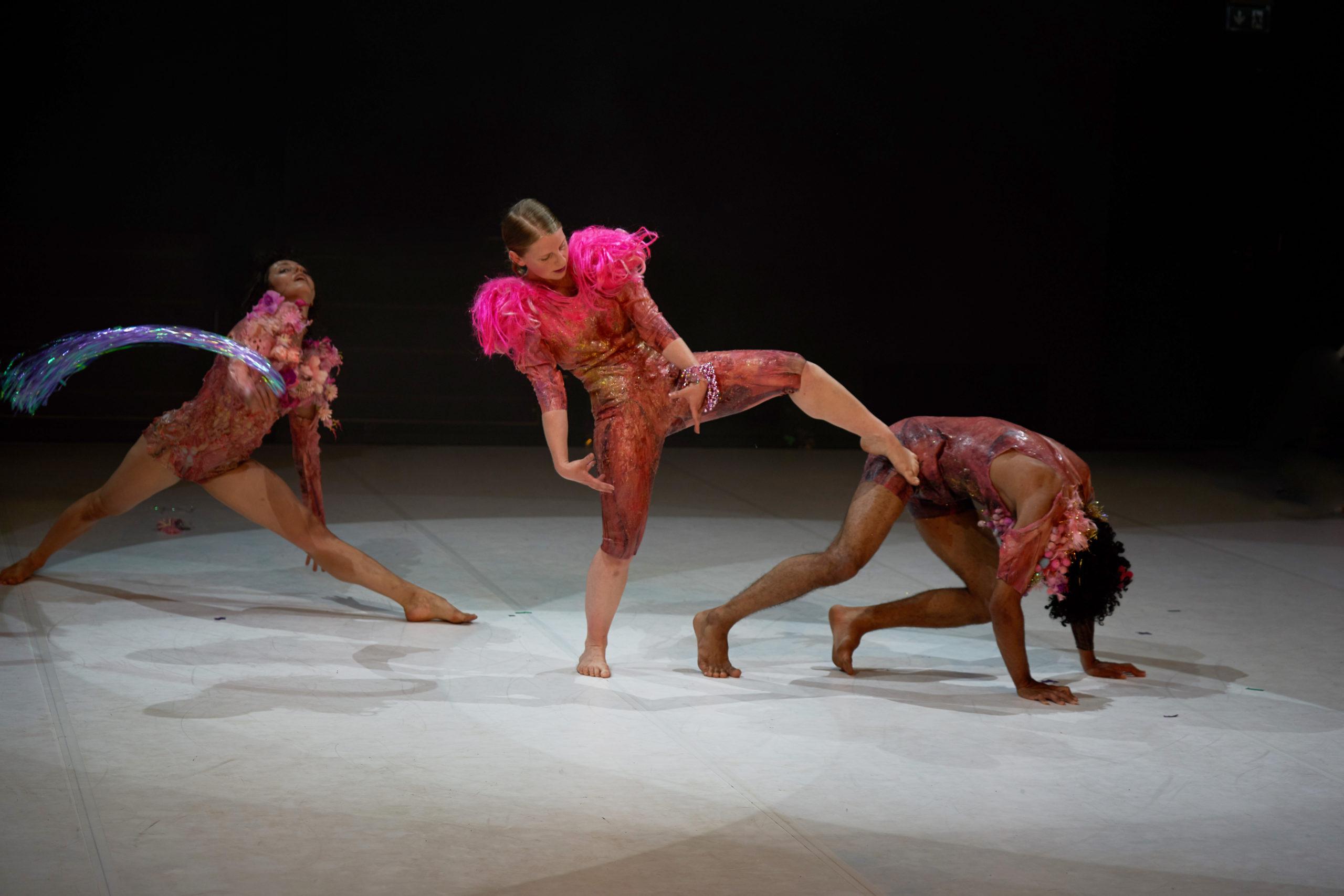 Szenenaufnahme der Forward Dance Companiy aus dem Stück JOY. Drei Tänzerinnen in rotbrauen Bodies auf der Bühne. Hellgrauer Bühnenboden, schwarzer Hintergrund. Lichtkegel über jeder Tänzerin. Die Tänzerin links steht im leichten Spagat nach vorn gebeugt, den Kopf nach hinten gelegt. Die tänzerin in der Mitte steht auf dem rechten Bein, das linke etwas angewinkelt, die Arme nach unten genommen und die Hände zueinander gedreht. Der Blick geht zur Tänzerin rechts, die auf allen vieren aussieht, als ob sie in den Startblöcken eines Sprints steht.