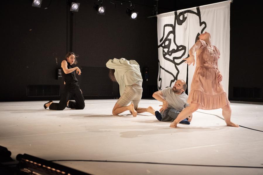 Szenenaufnahme der Forward Dance Companiy aus dem Stück WIR. Aufnahme von der rechten Seite auf die Bühne. Hellgrauer Bühnenboden, schwarzer Hintergrund vor dem ein großes weißes Textil hängt, auf dem eine schwarze Grafik ein abstrahiertes Gesicht zeigt. Auf der Bühne vier Tänzerinnen. Die Tänzerin links ist schwarz gekleidet und kniet zu den anderen Tänzerinnen gewendet. Ihr gegenüber eine weitere knieende Tänzerin in weiß. Als drittes ein kleiner Tänzer auf den Boden in grauer Kleidung und als vierte eine stehende Tänzerin im hellrosa Kleid von allen anderen abgewendet, leicht im Schritt, in die Knie gehend und den Kopf nach hinten werfend.