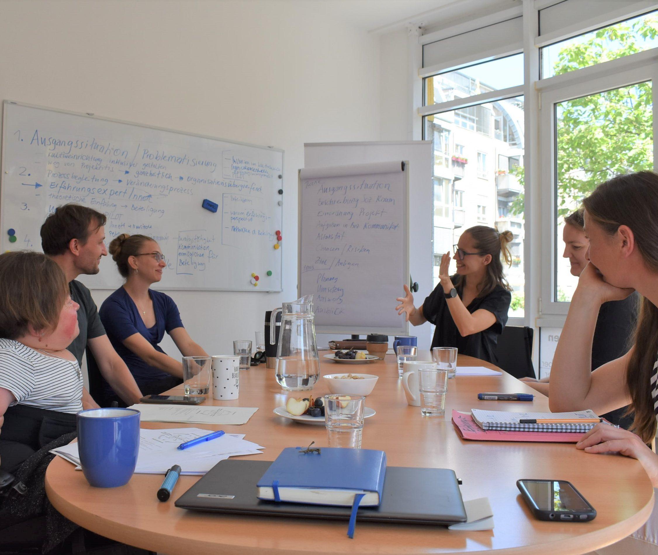Das Foto zeigt eine Gruppe von Personen, die an einem Tisch sitzen und sich unterhalten..