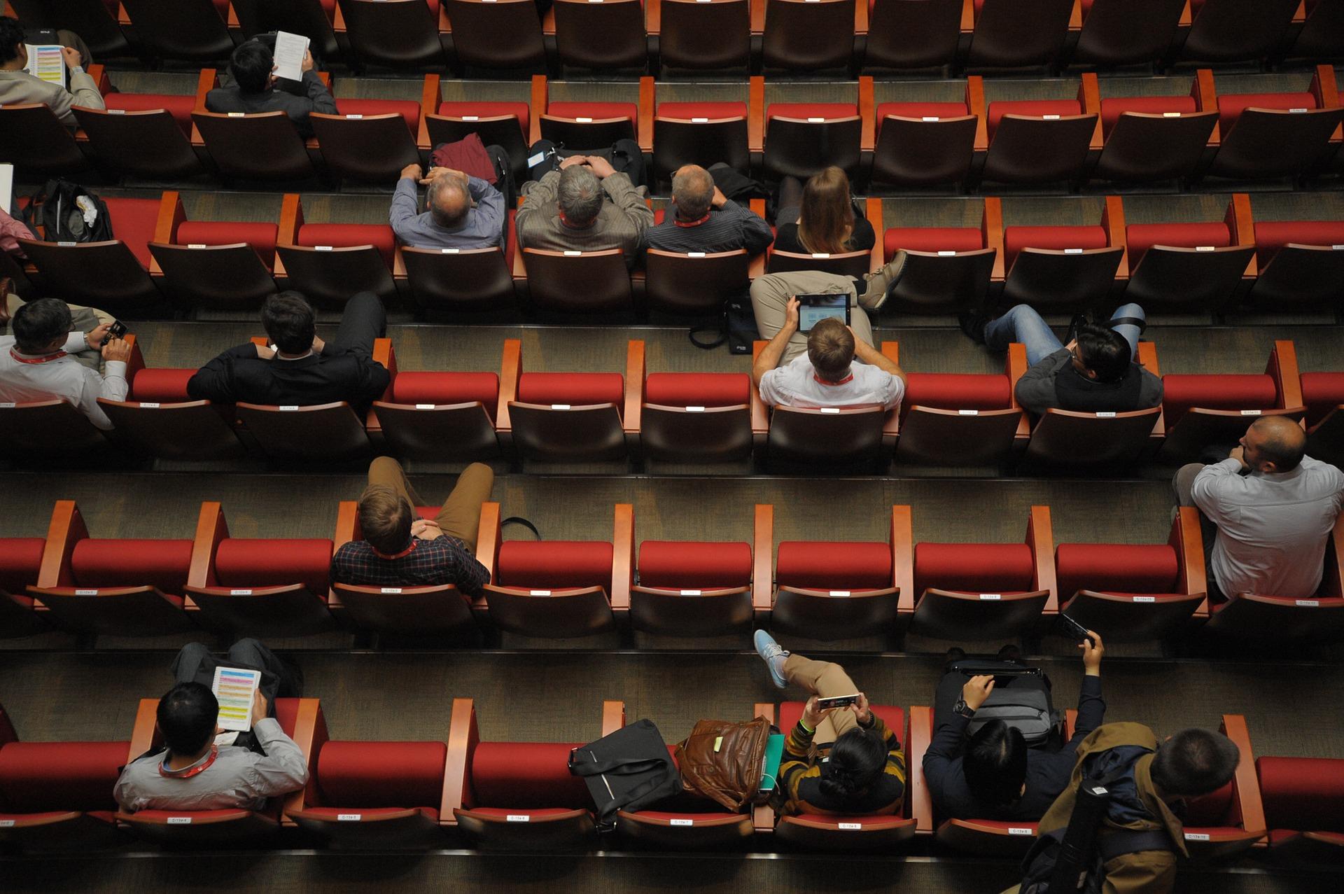 Das Foto zeigt ein Auditorium von oben. Das Auditorium ist mit roten Samtstuhlreihen bestuhlt. Die Stühle sind lückenhaft besetzt. Einige Personen haben einen Laptop auf dem Schoß.
