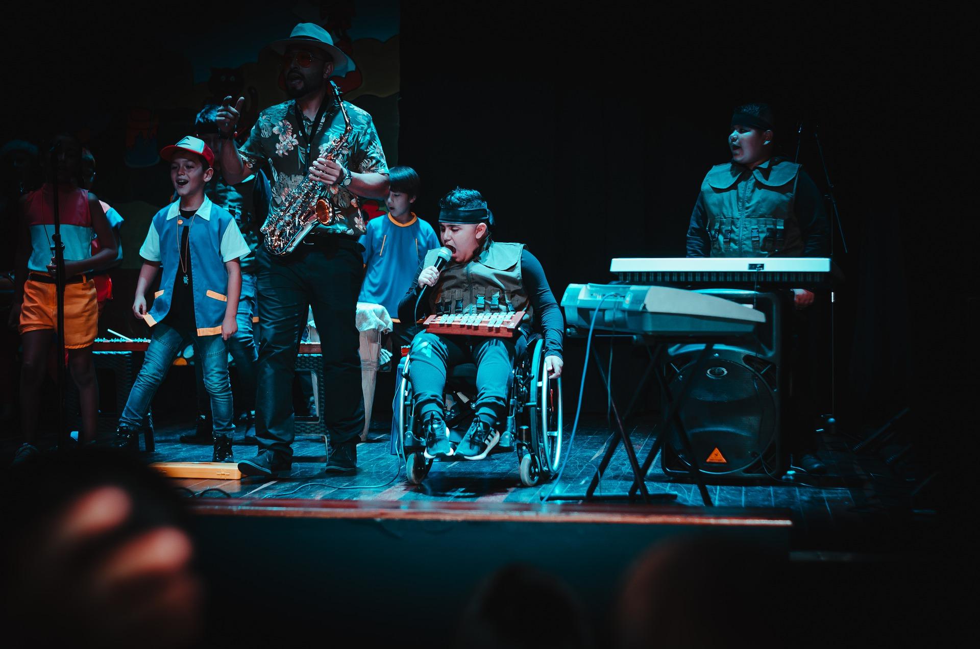 Das Foto zeigt eine sechsköpfige Kinderband beim Auftritt. Mittig der Sänger im Rollstuhl, er hält ein Mikrofon in der Hand.
