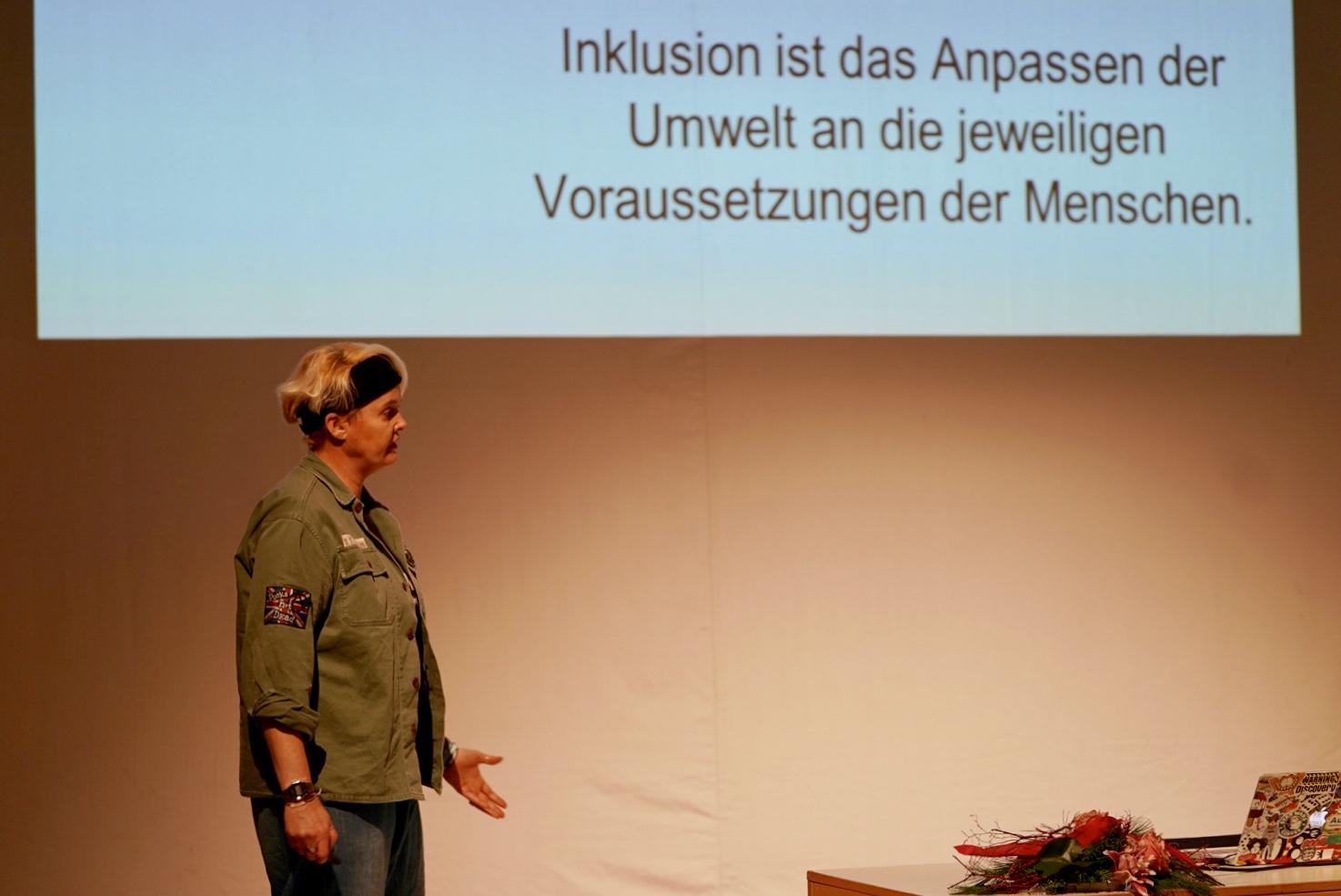 Das Foto zeigt eine Frau vor einen gelb-braunen Hintergrund. In der rechten oberen Bildhälfte ist ein schwarzer Schriftzug an die Wand projiziert. Dort steht: Inklusion ist das Anpassen der Umwelt an die jeweiligen Voraussetzungen der Menschen.