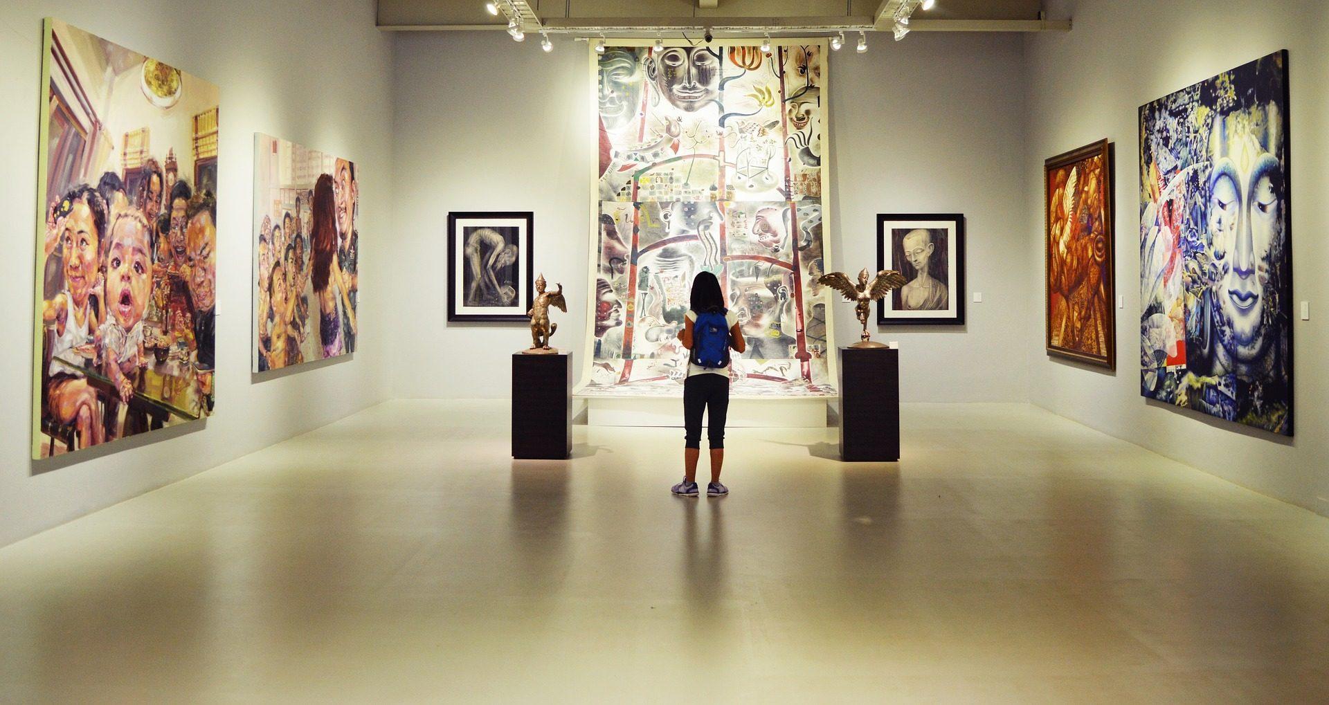 Das Foto zeigt einen Ausstellungsraum, der rechts, links und im hinteren Bereich durch drei weiße Wände begrenzt ist. Vor der hinteren Wand steht eine Besucherin mit dem Rücken zum Betrachter. Sie trägt einen Rucksack und schaut sich das Bild auf der hinteren Wand an. Das Bild reicht von der Decke bis zum Fußboden. Rechts und links des Bildes stehen zwei schwarze Sockel mit Ausstellungsobjekten. Rechts und links neben dem großen Bild hängen zwei kleinere Portraits, jeweils von schwarzen Rahmen umrahmt. An der rechten und linken Wand hängen jeweils zwei großformatige Leinwände.
