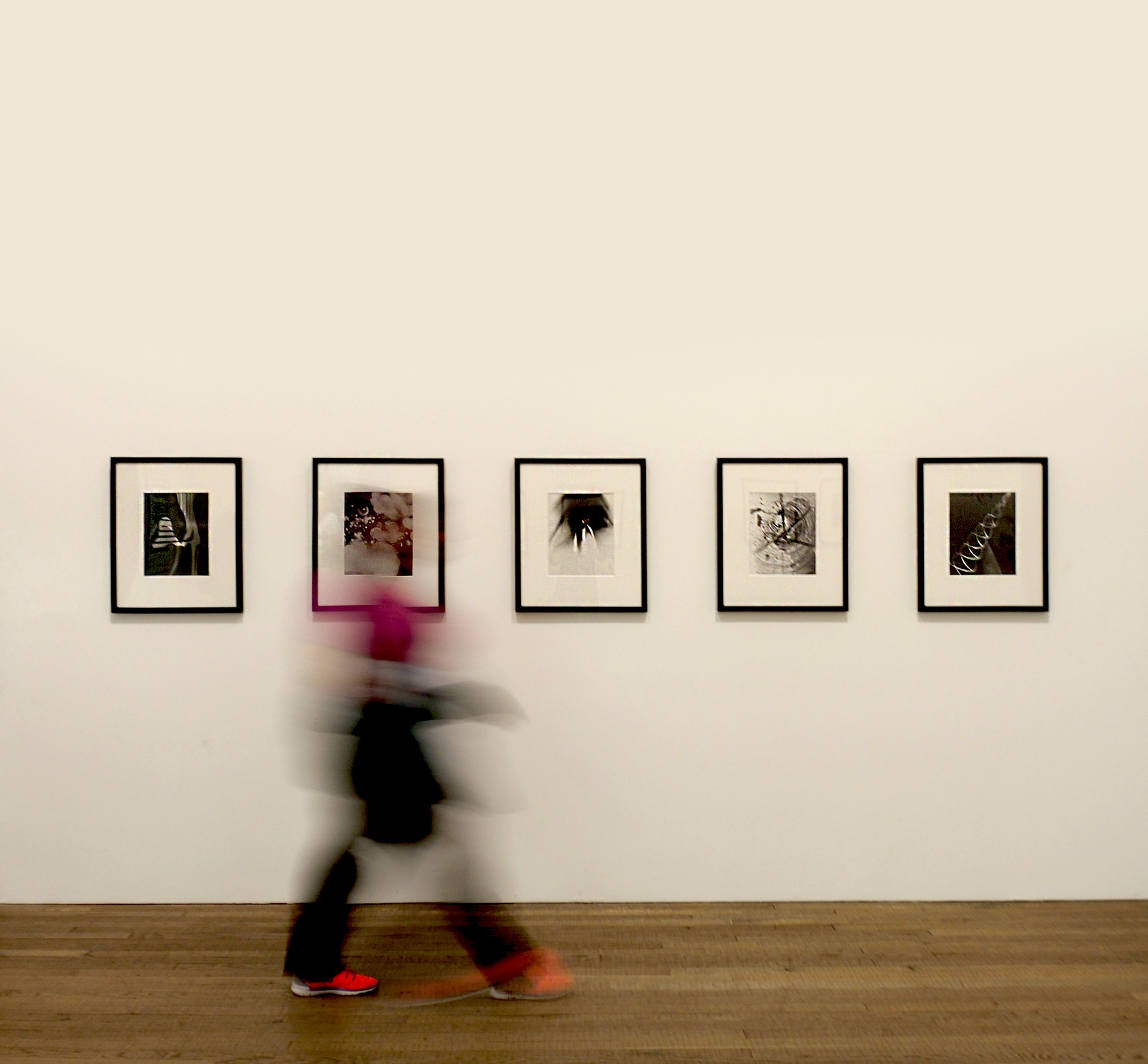 Das Foto zeigt eine weiße Wand, an der fünf schwarz gerahmte Bilder aufgehängt sind. Eine Person läuft an den Bildern von links nach rechts vorbei. Während die Bilder im Hintergrund scharf sind, ist die Person im Vordergrund verschwommen.